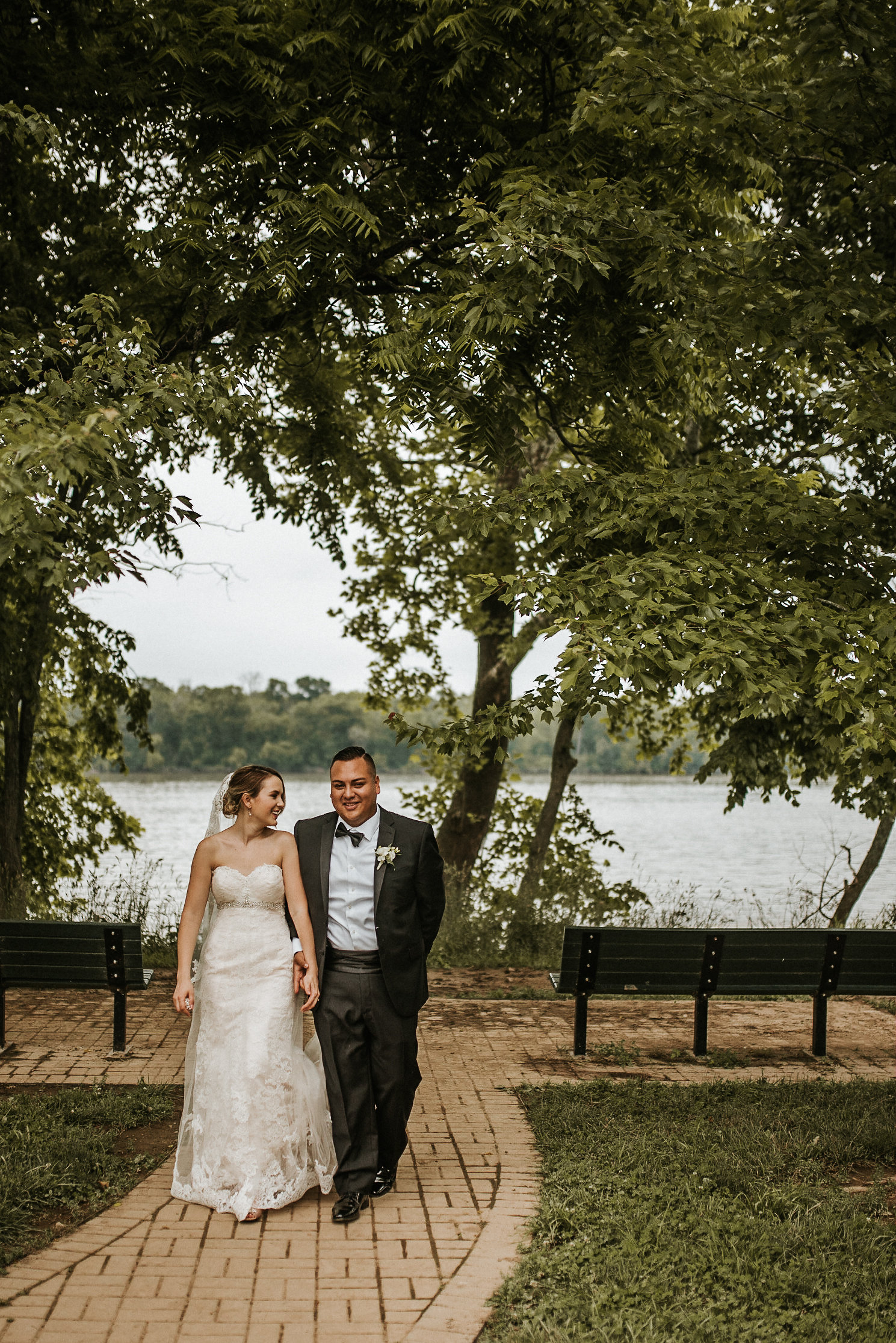 Bride and groom walking away from lake