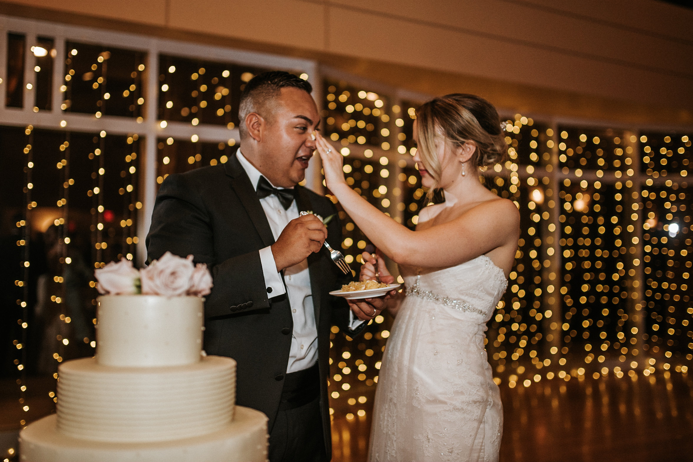 Bride putting cake on groom's nose