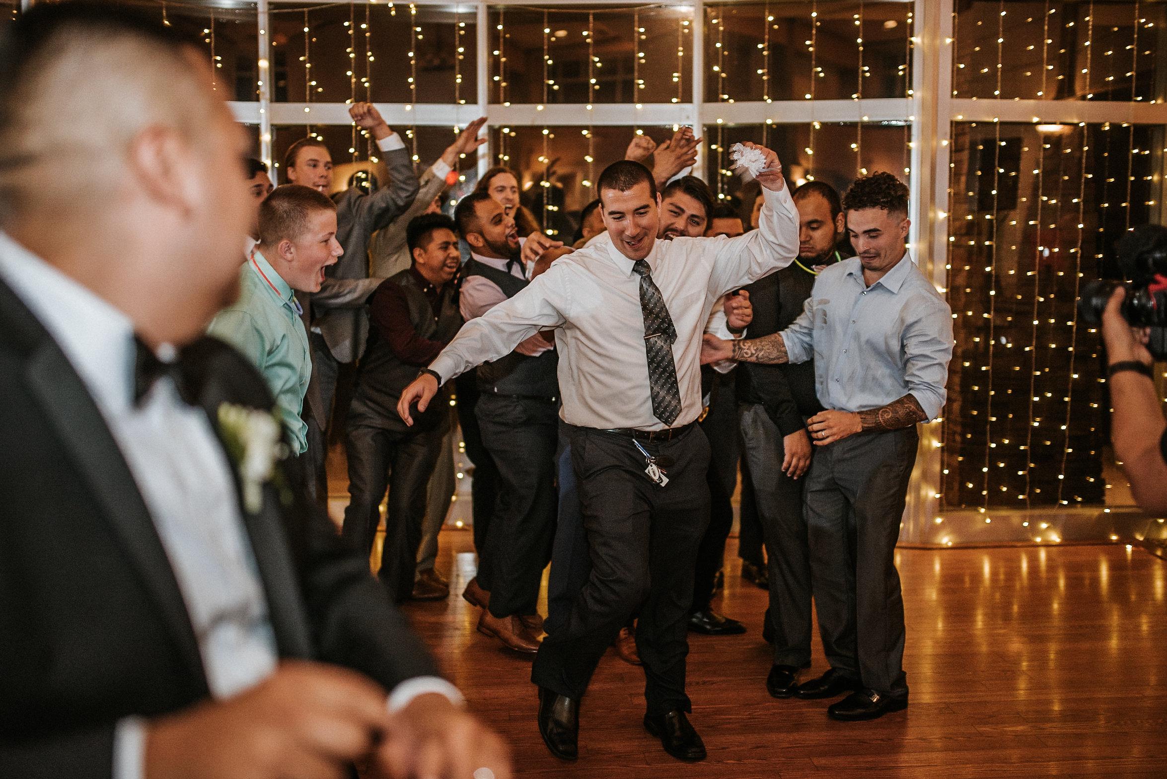 Men catch garter at wedding