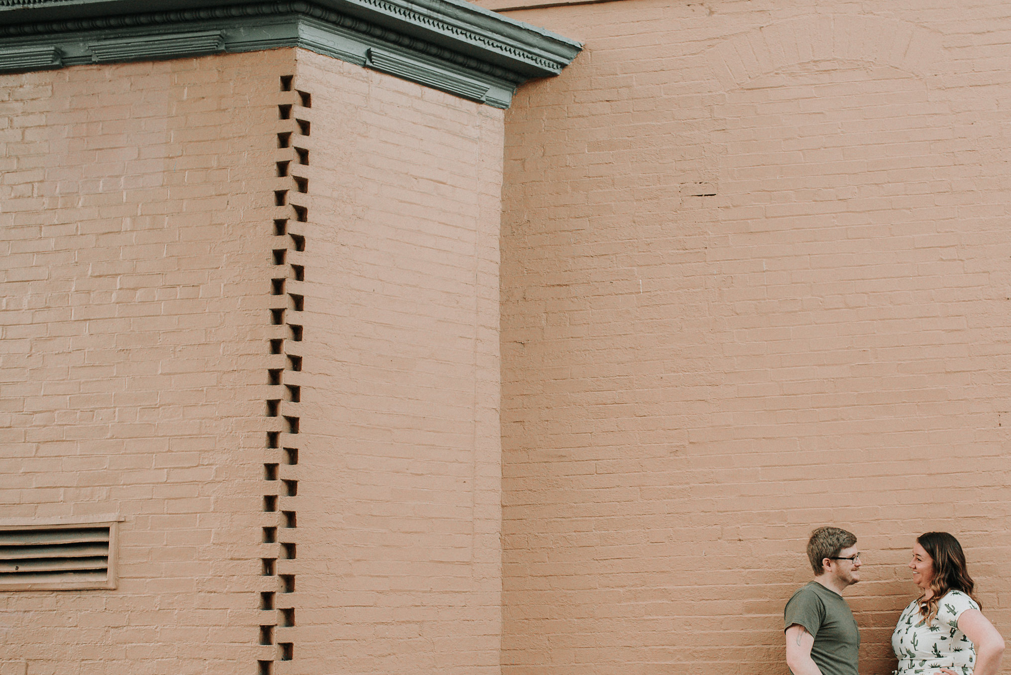 Couple talking by brick wall