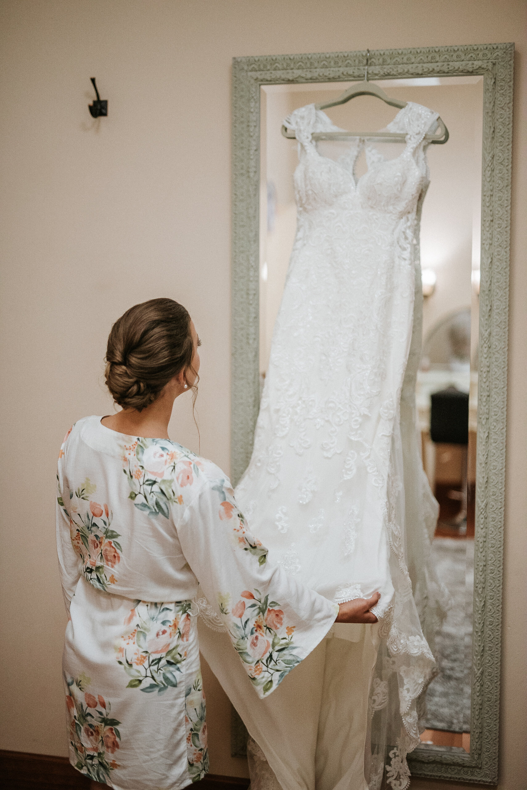 Bride looking at dress on hanger