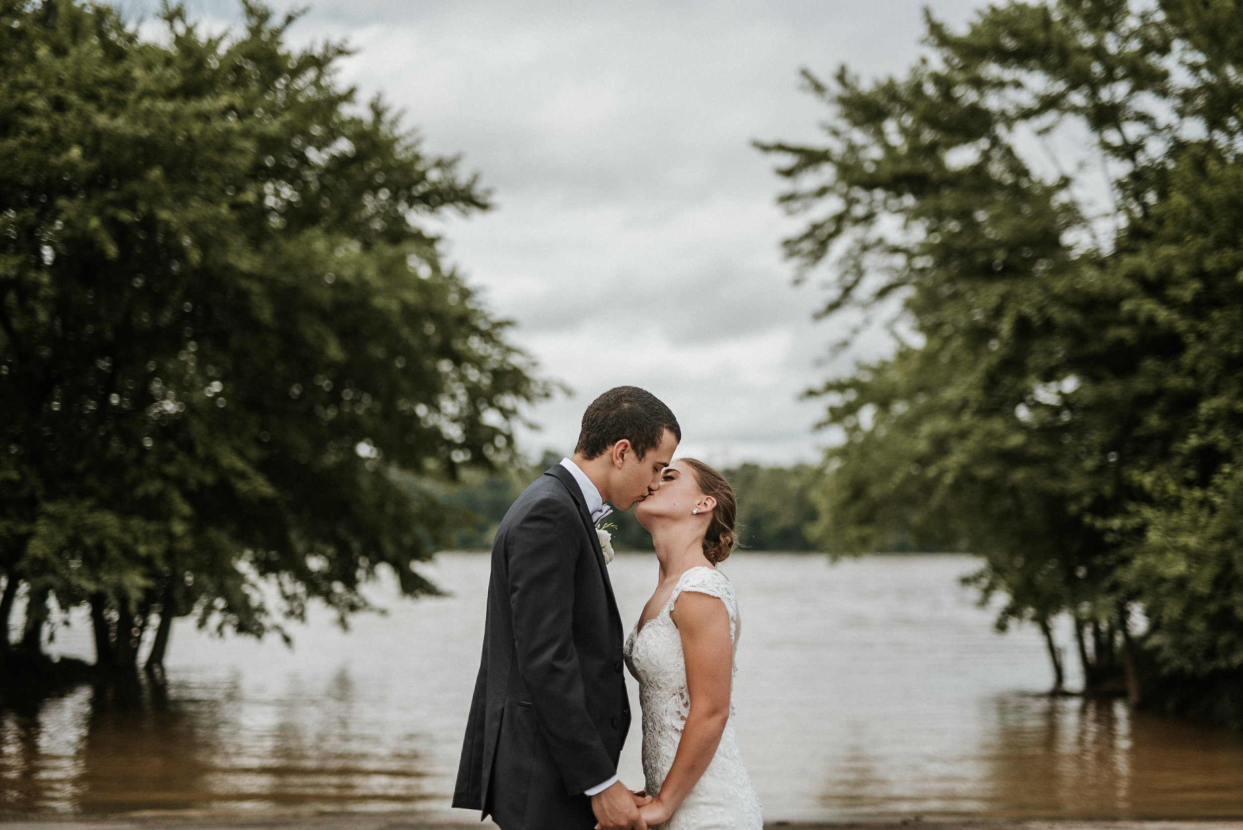 Bride and groom kissing in front of flooding