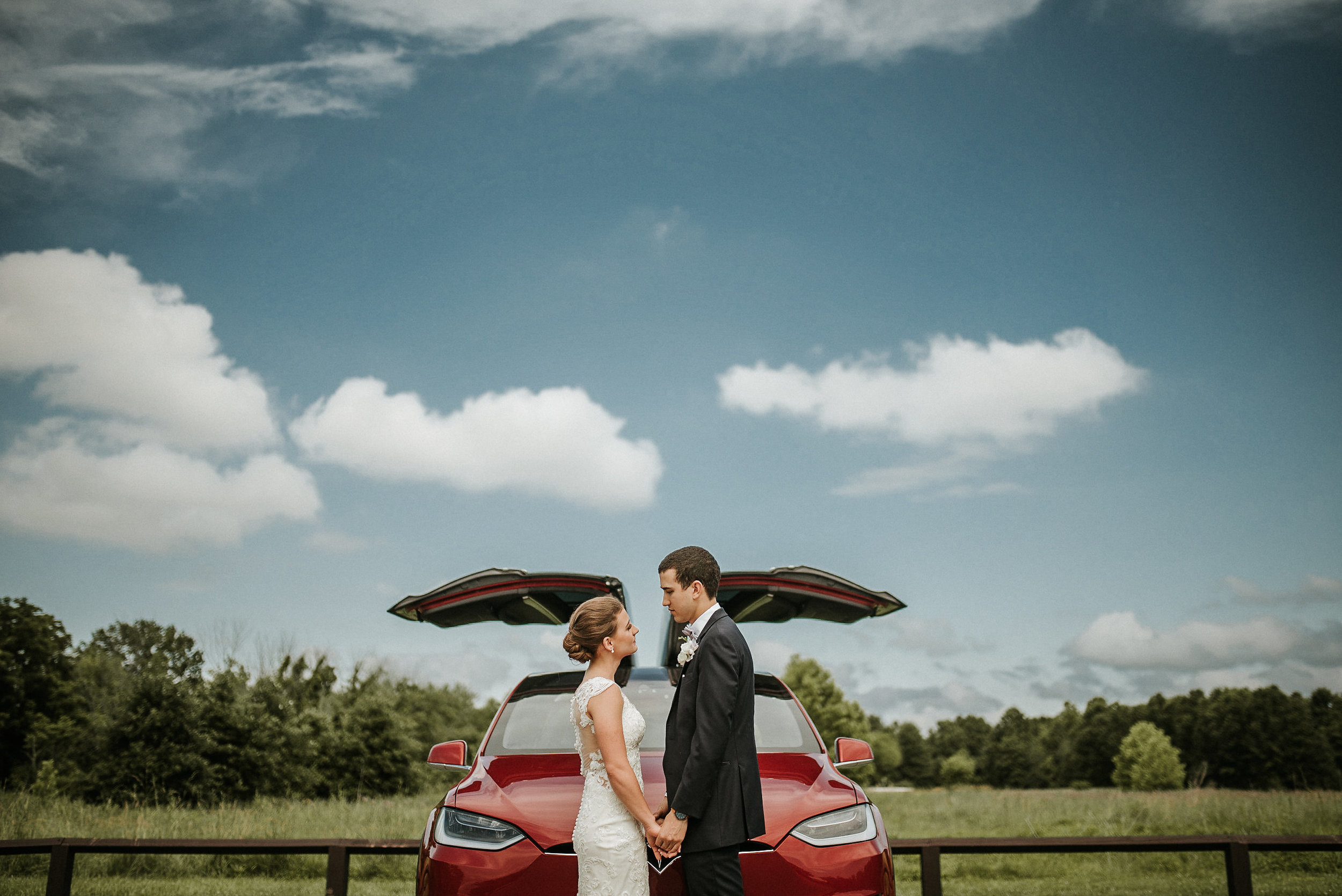 Bride and groom in front of Tesla