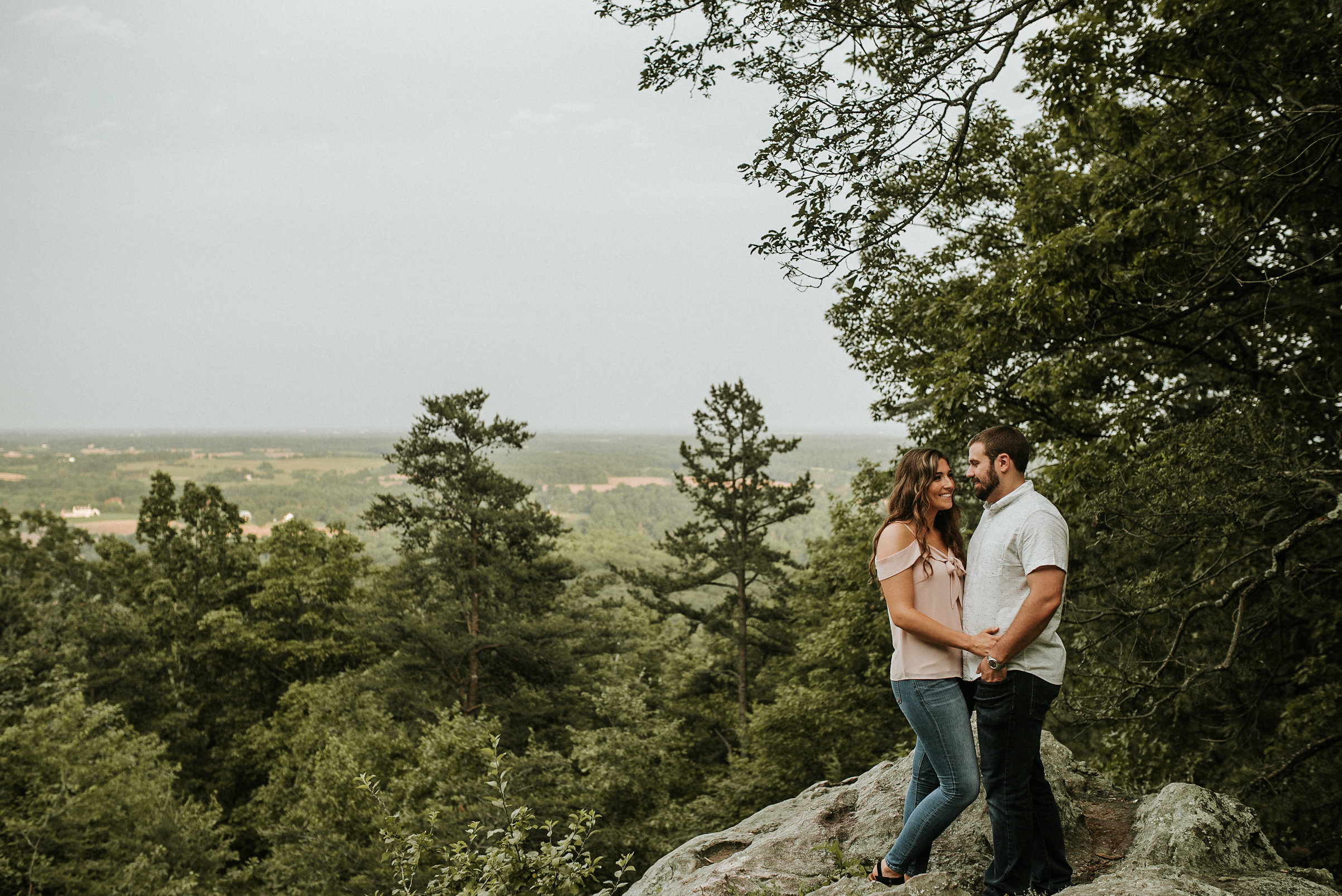 Couple standing on rock on mountain