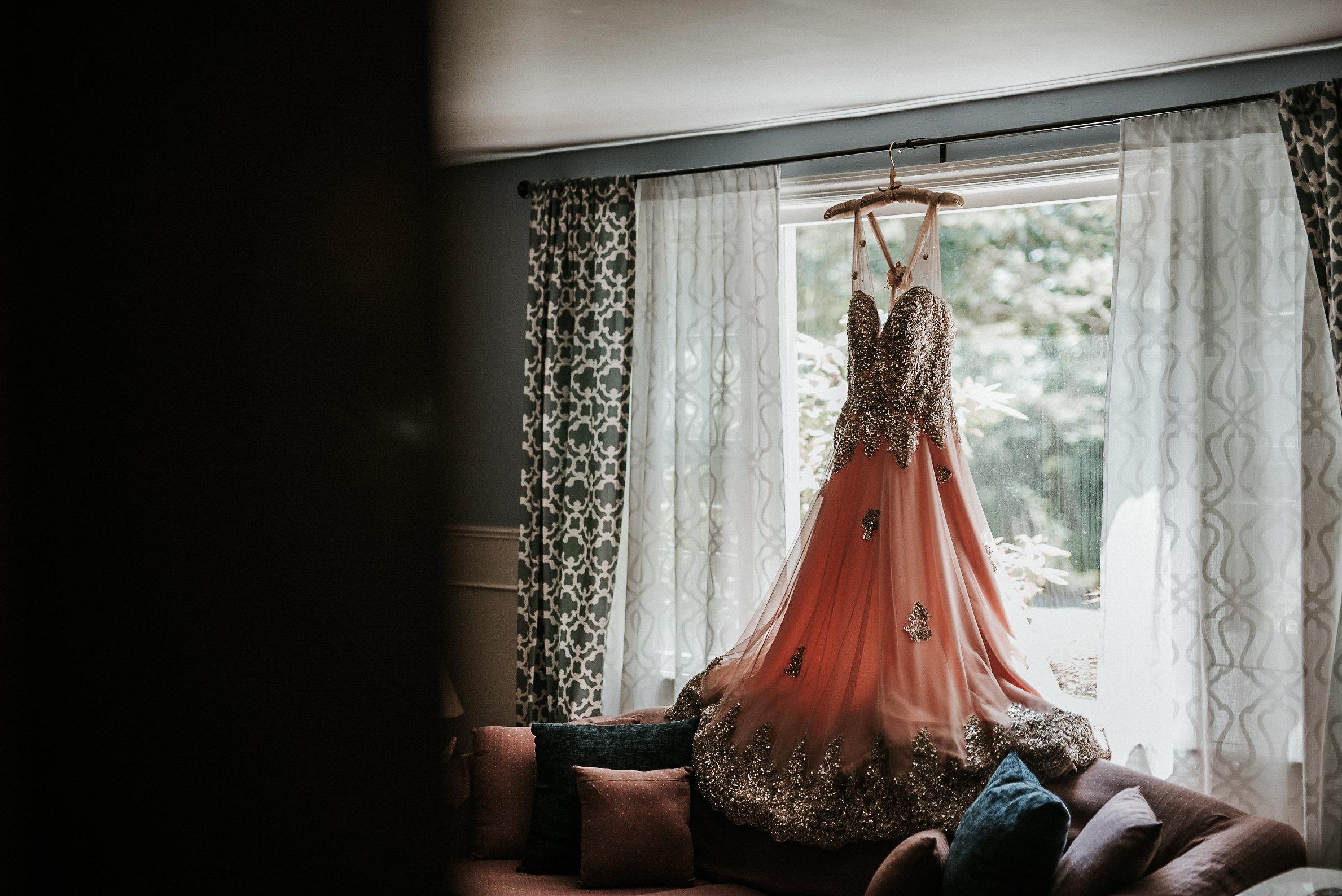 Pink wedding dress hanging in window