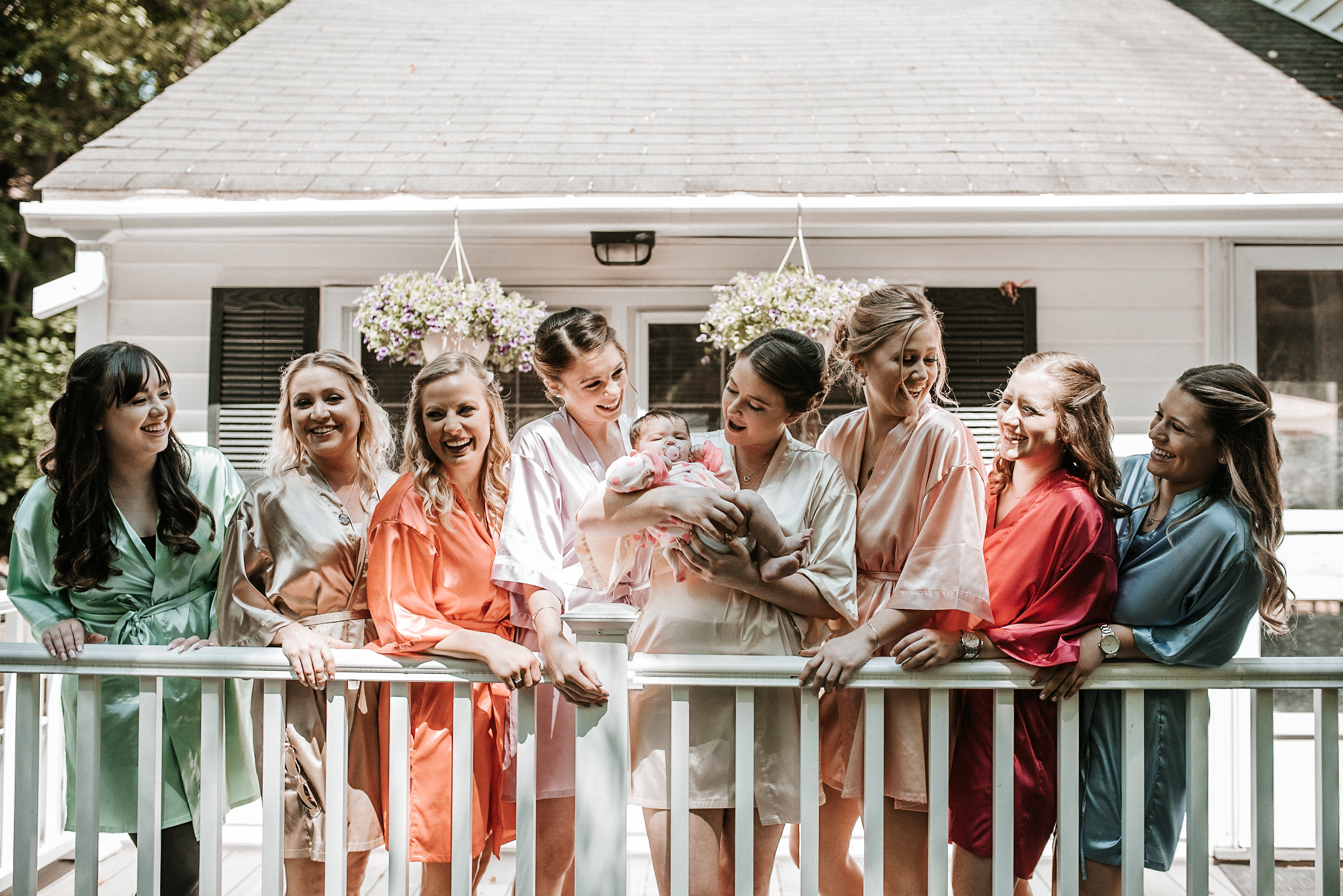 Bride holding baby surrounded by bridesmaids