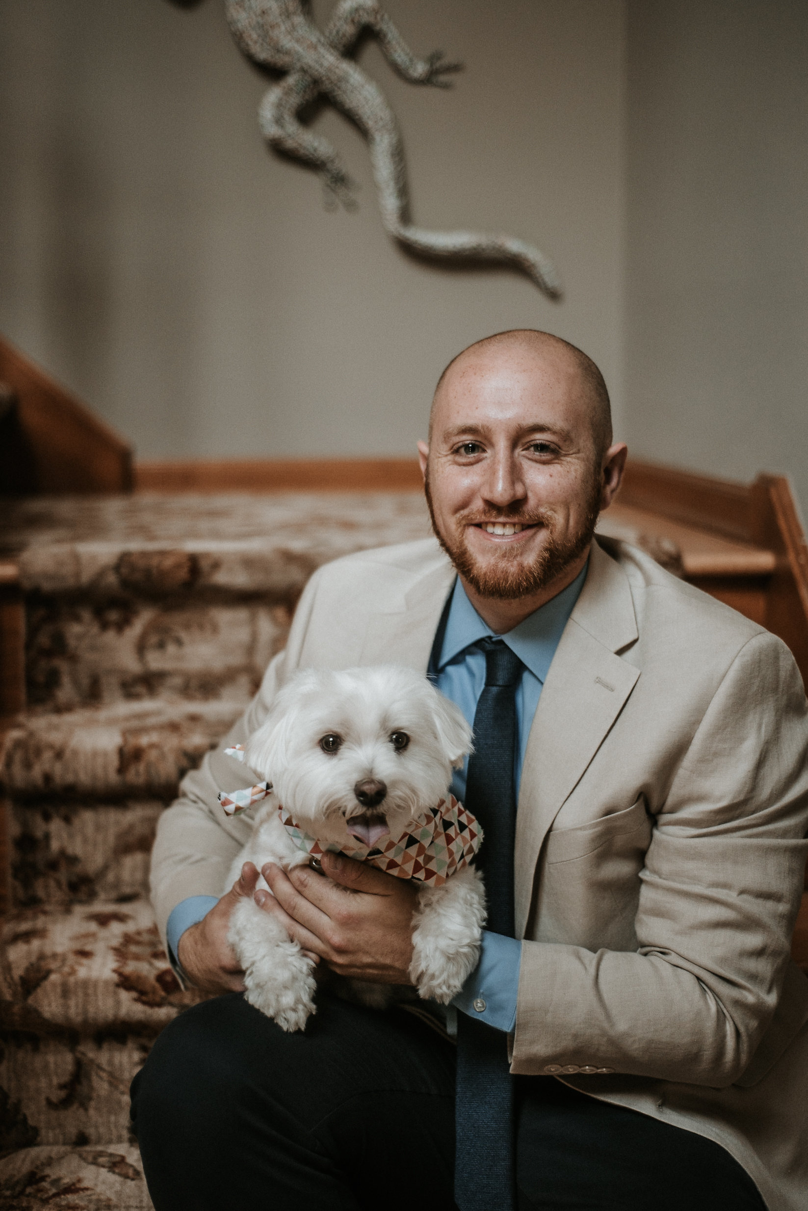 Groom holding dog on stairs