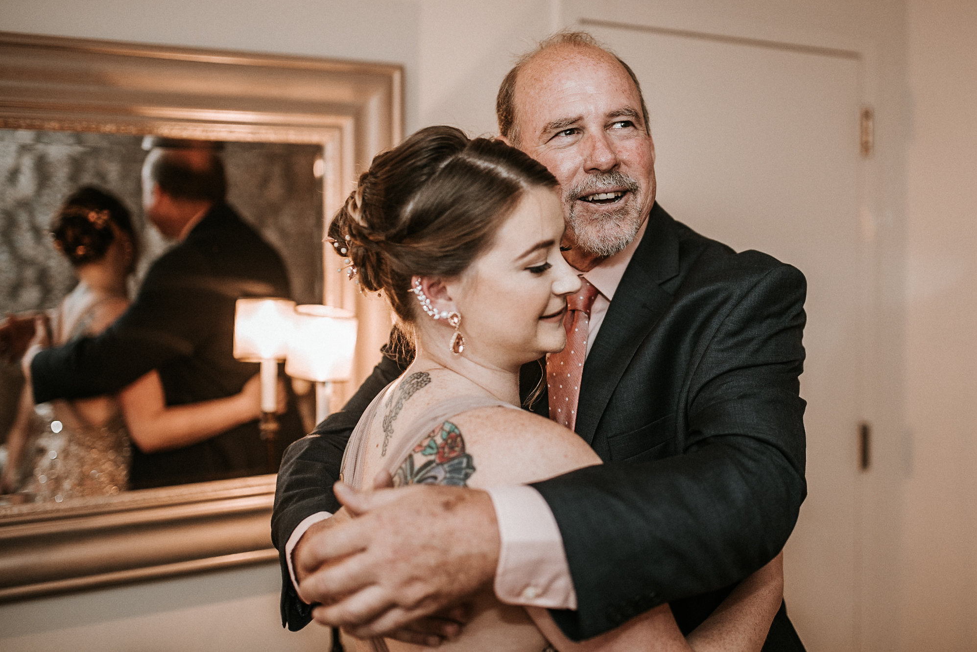 Bride and father hugging before wedding