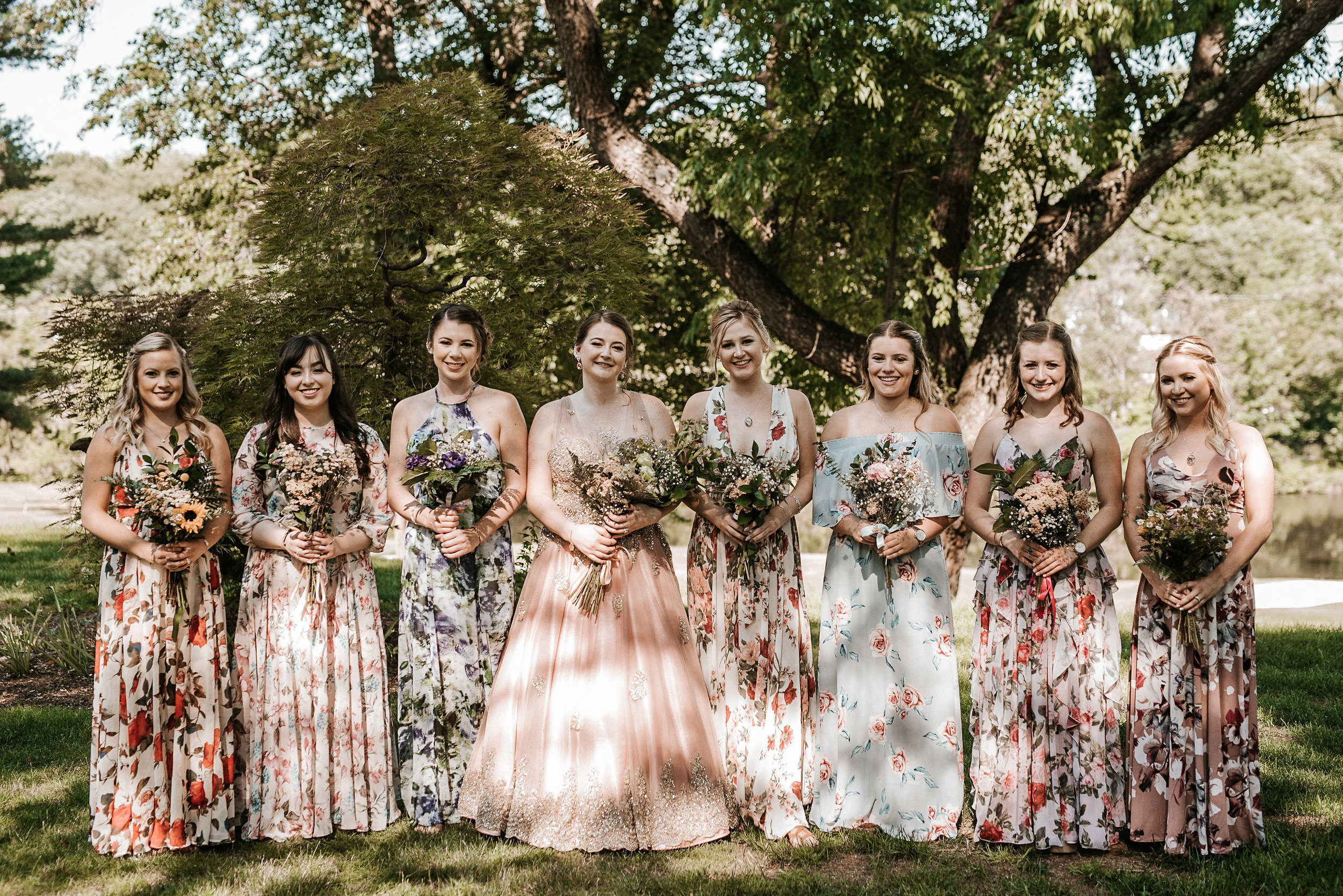 Bride and all the bridesmaids under a tree