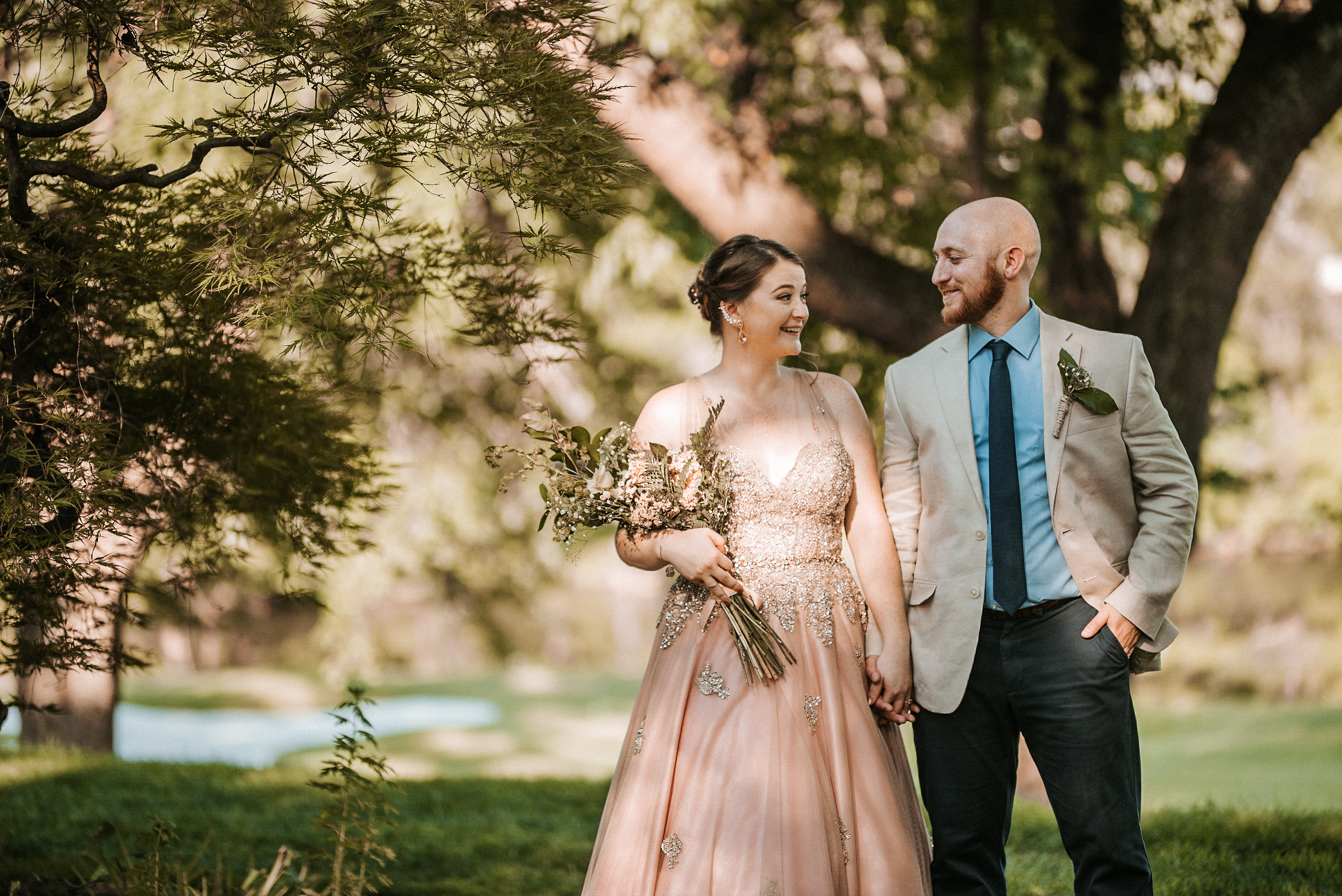 Bride and groom under tree on golf course