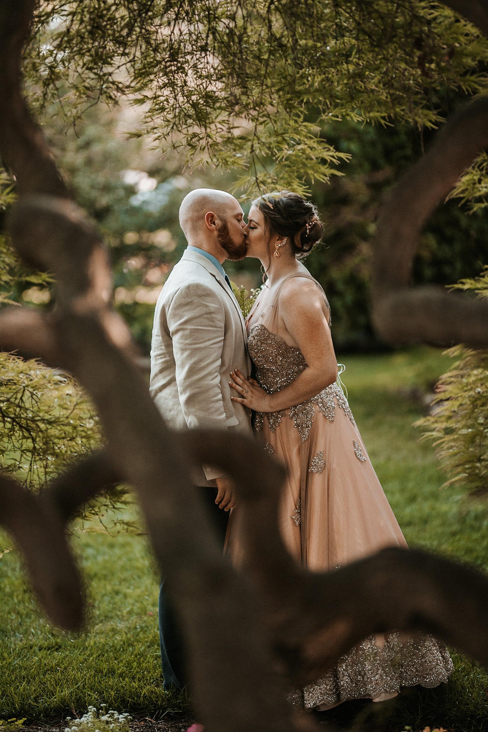 Bride and groom kissing behind tree