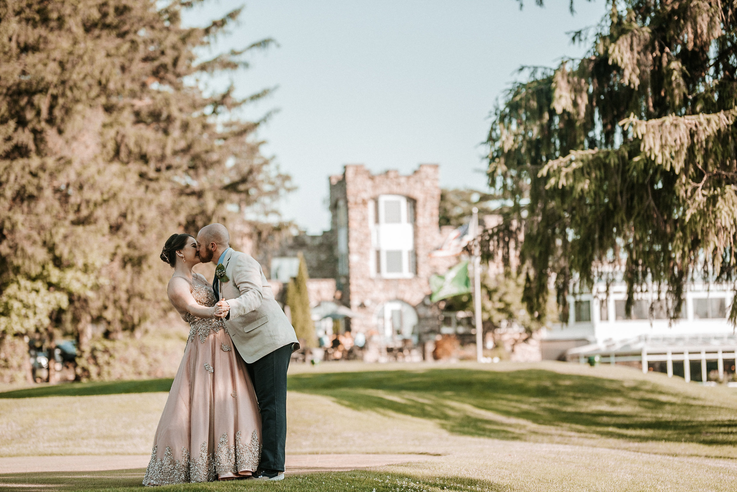 Bride and groom kissing in front of country club castle