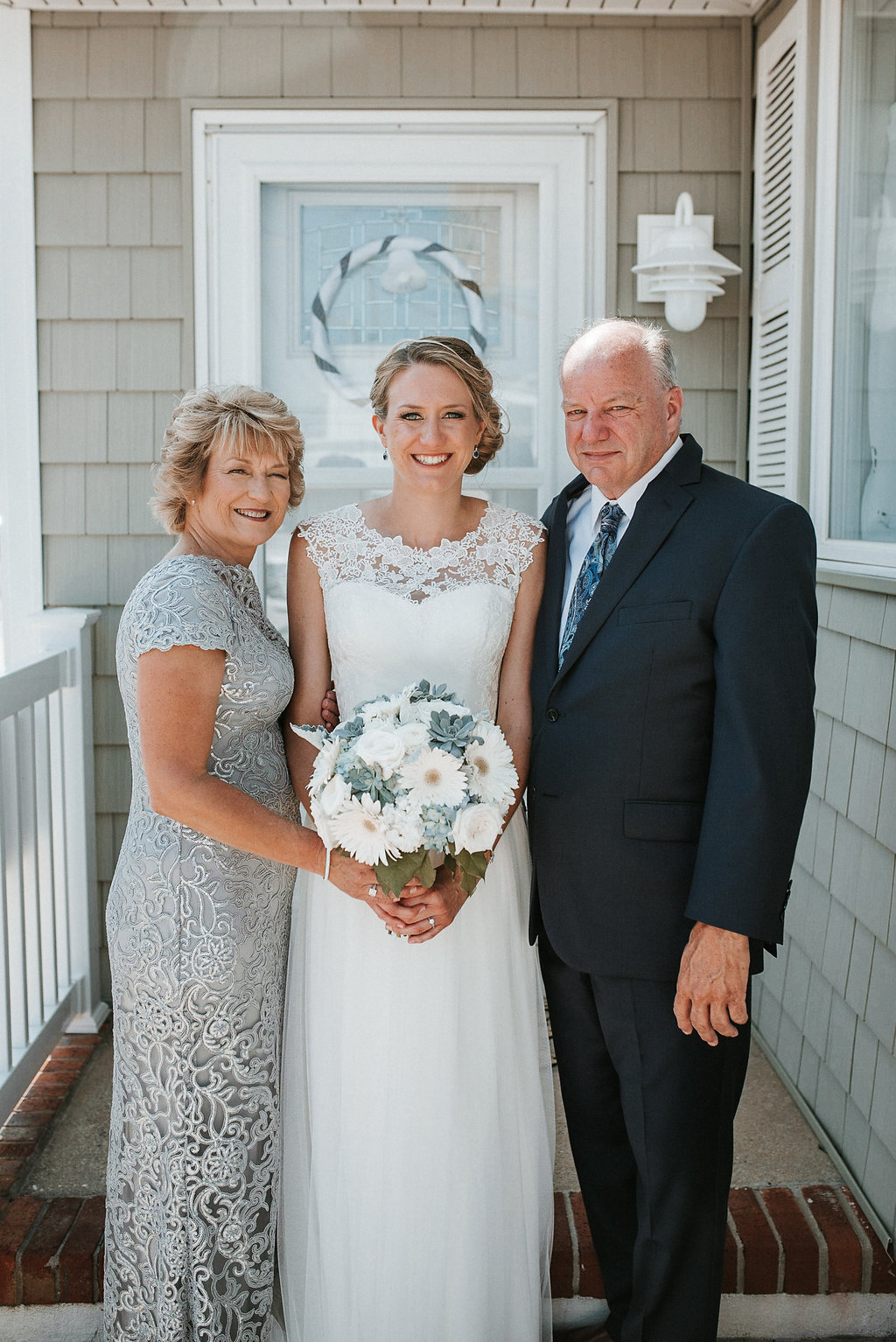 Bride with mother of the bride and father of the bride at crystal point yacht club