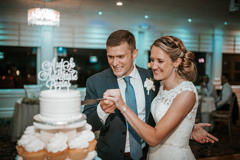 Bride and Groom cutting the cake at crystal point yacht club