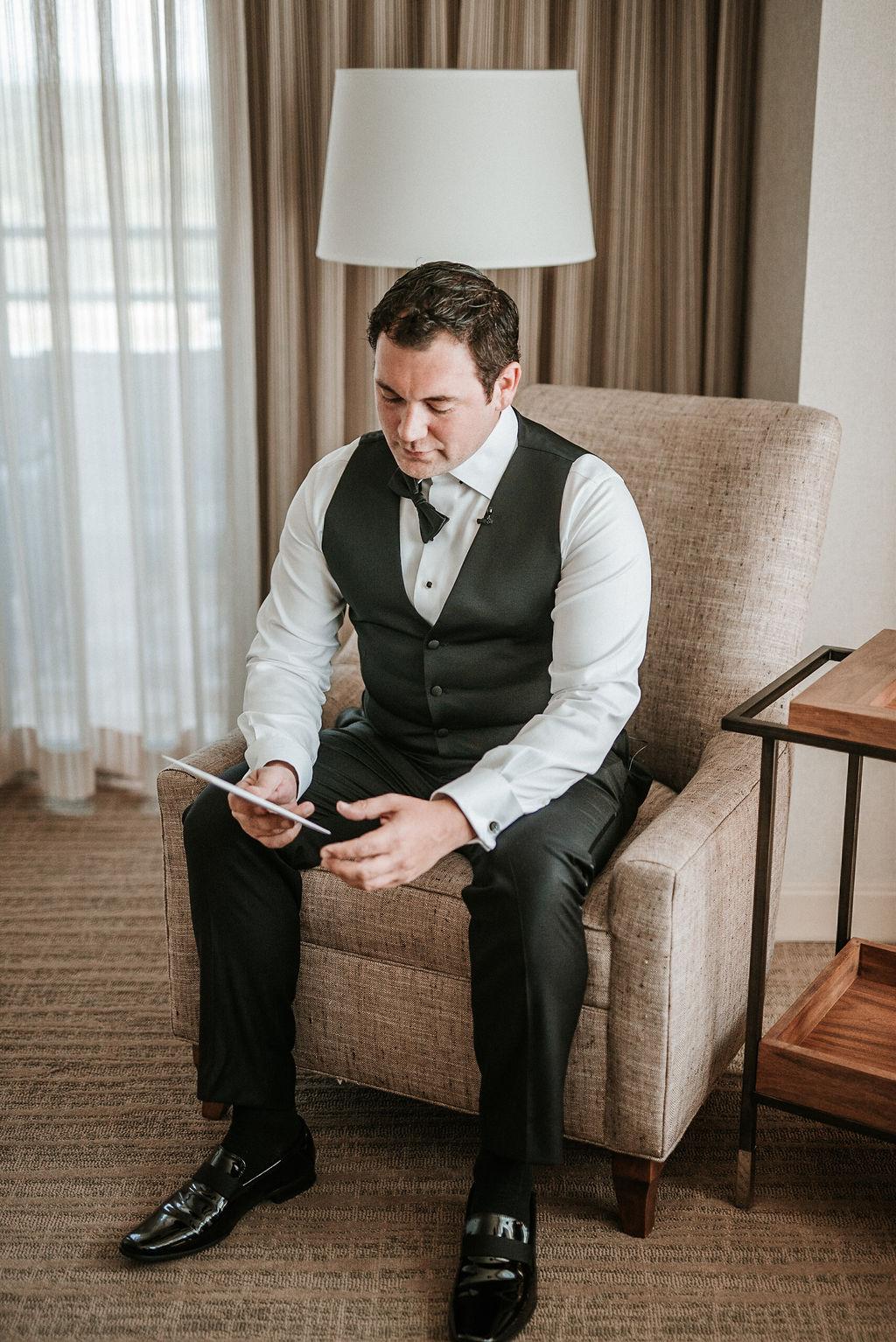 Groom reading letter from bride at Bluemont Vineyard