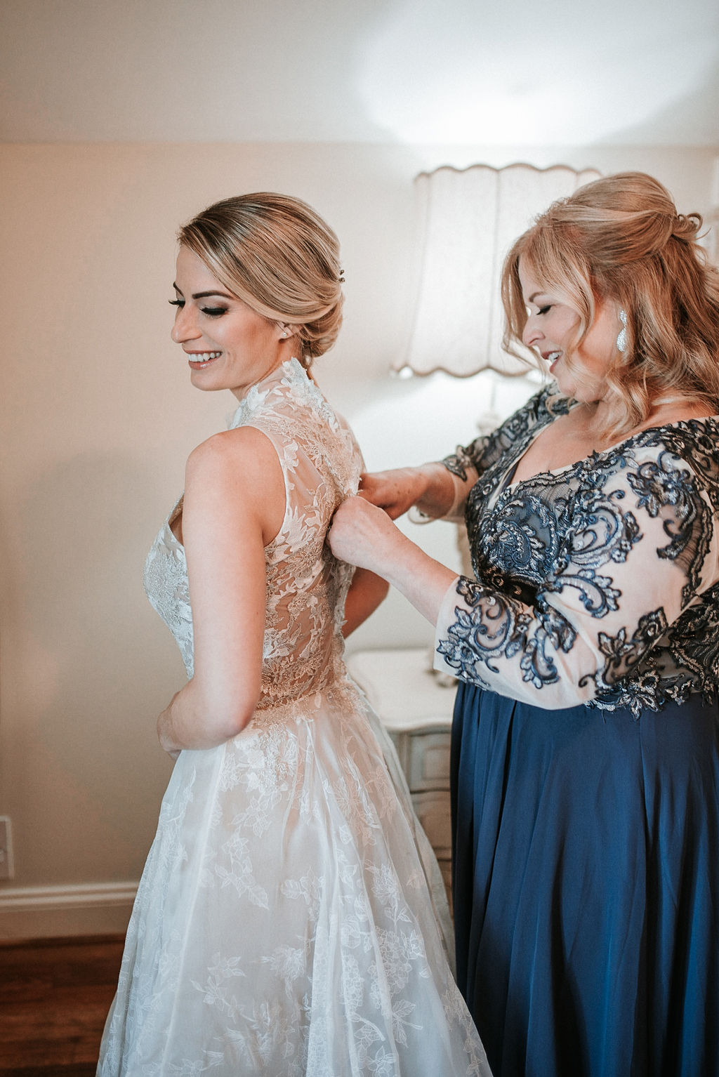 Mother of the Bride helping Bride get into Wedding dress at Bluemont Vineyard