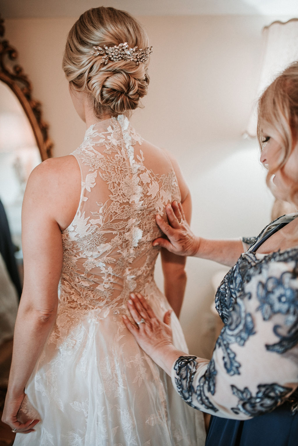 Mother of the Bride helping button Bride's wedding dress at Bluemont Vineyard
