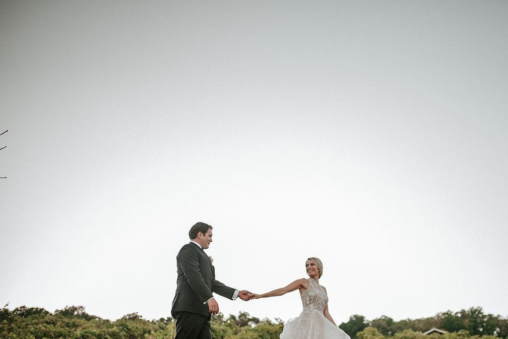 Bride and Groom Walking through vineyards at Bluemont Vineyard