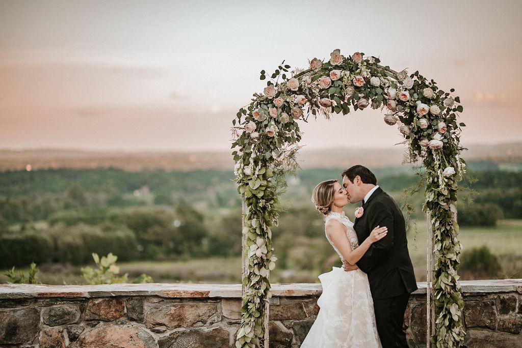 Bride and Groom Kissing at Sunset at Alter at Bluemont Vineyard