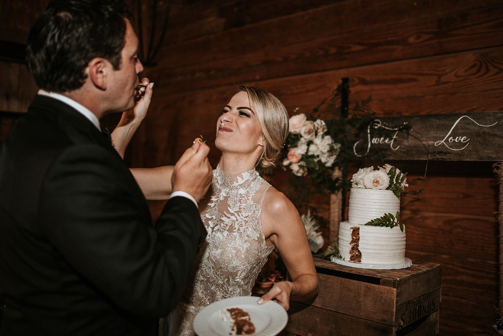 Bride and Groom Feeding each other wedding cake at Bluemont Vineyard