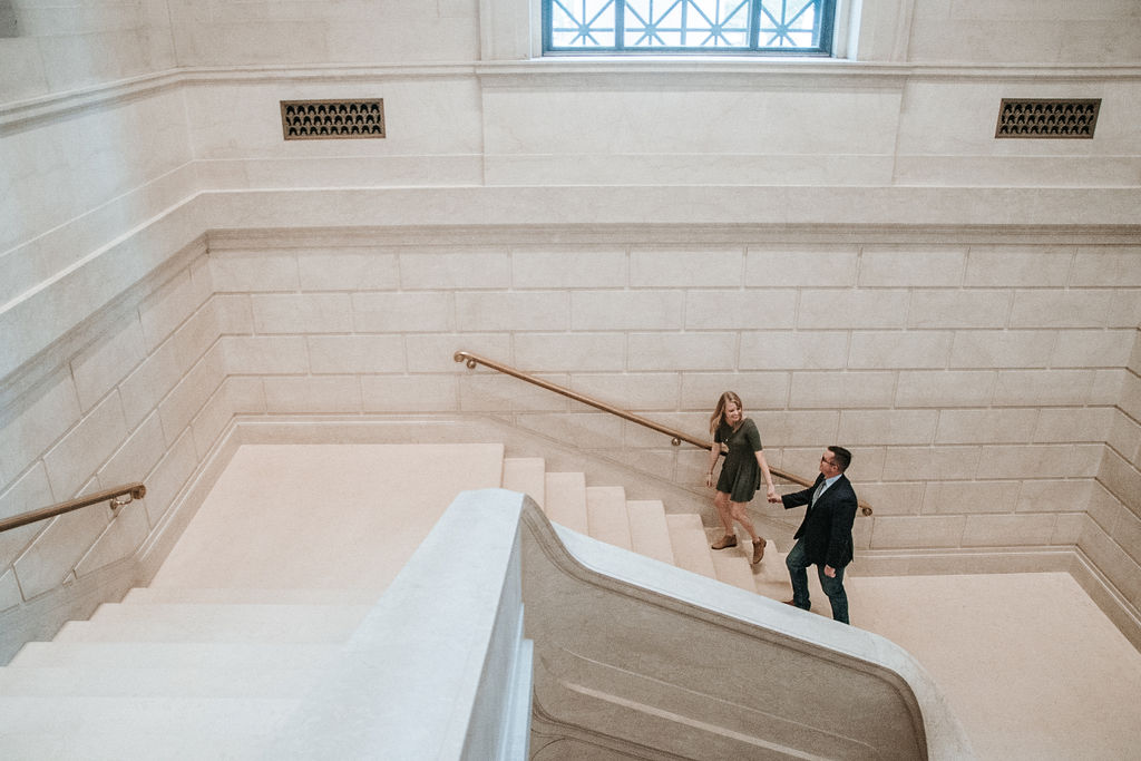 Couple walking upstairs at engagement shoot at Smithsonian National Portrait Gallery