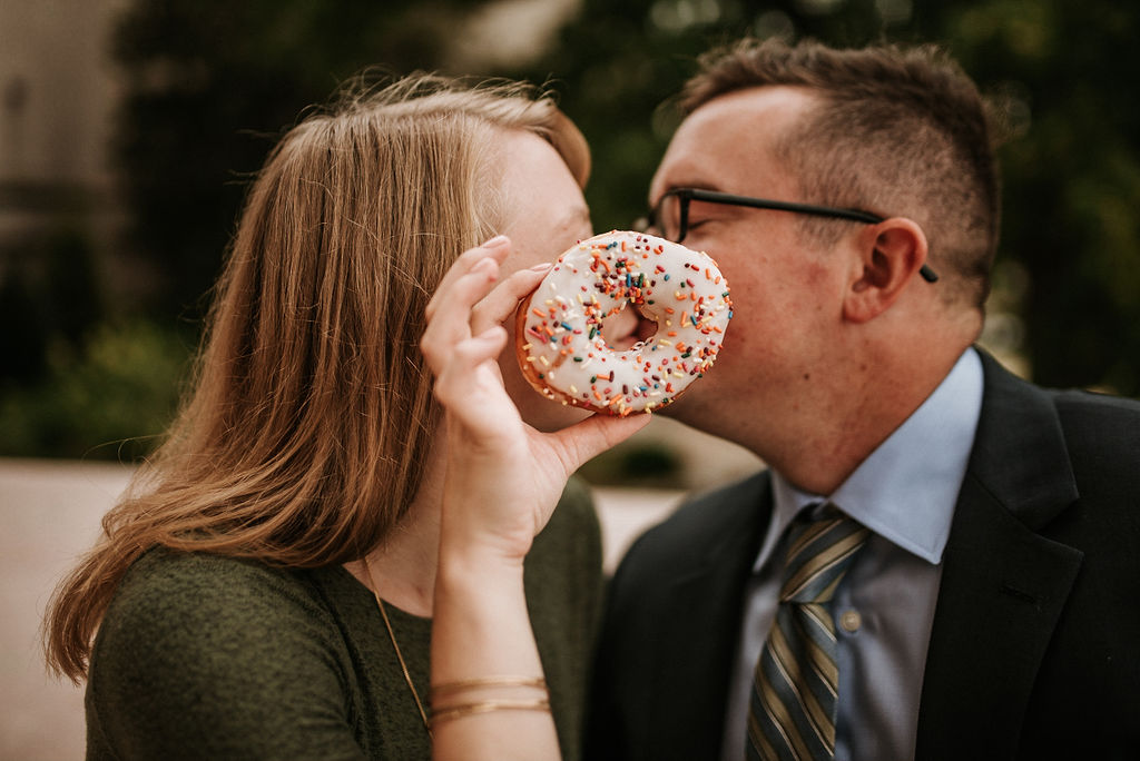 couple kissing behind donut during engagement session at Smithsonian National Portrait Gallery