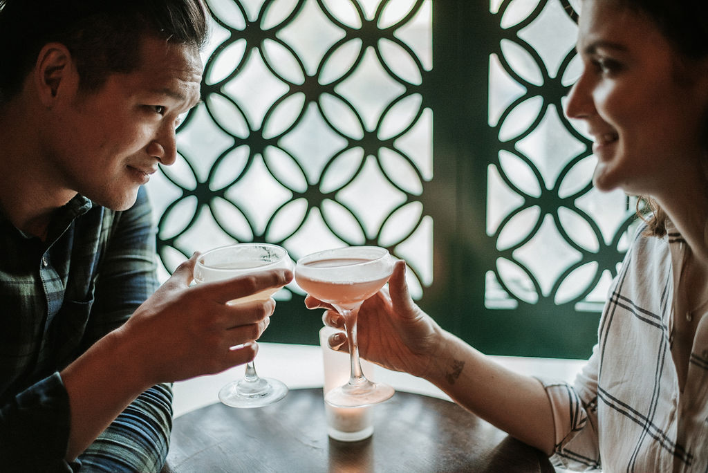 couple clinking glasses during engagement session at H Street in Washington DC