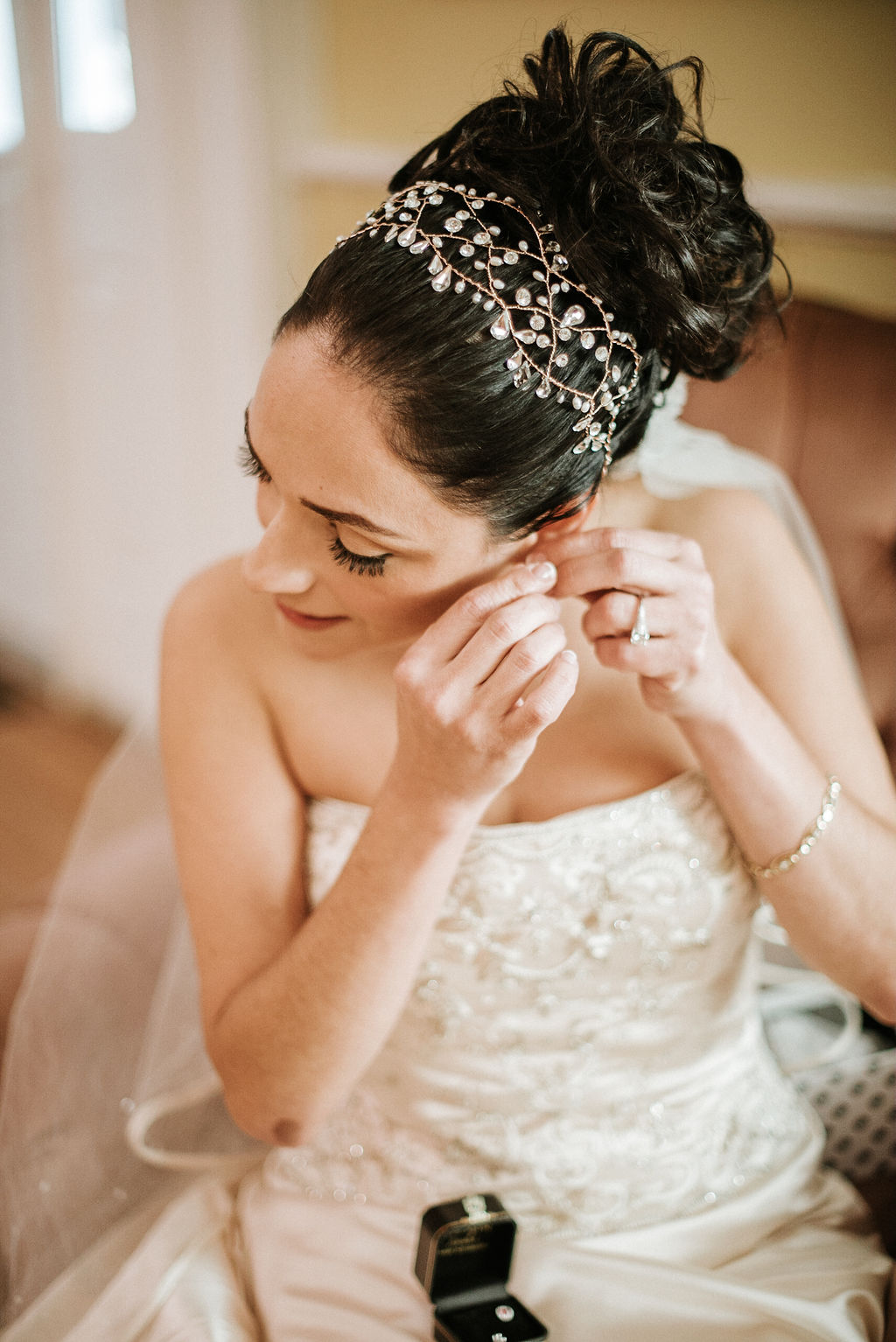 bride putting on earrings at Inn at the Old Silk Mill