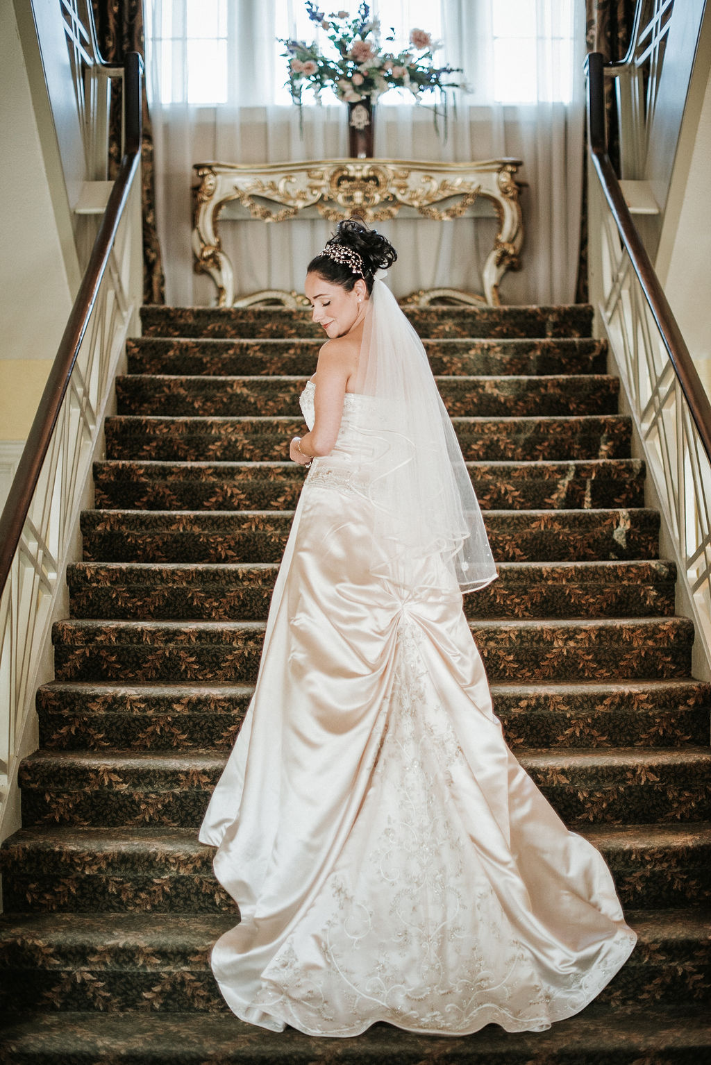 Bride posing on staircase at Inn at the Old Silk Mill