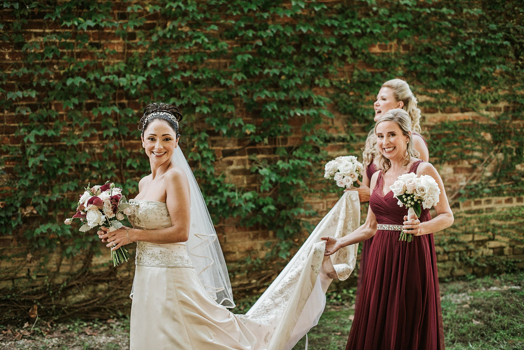 Bride walking with bridesmaids at Inn at the Old Silk Mill