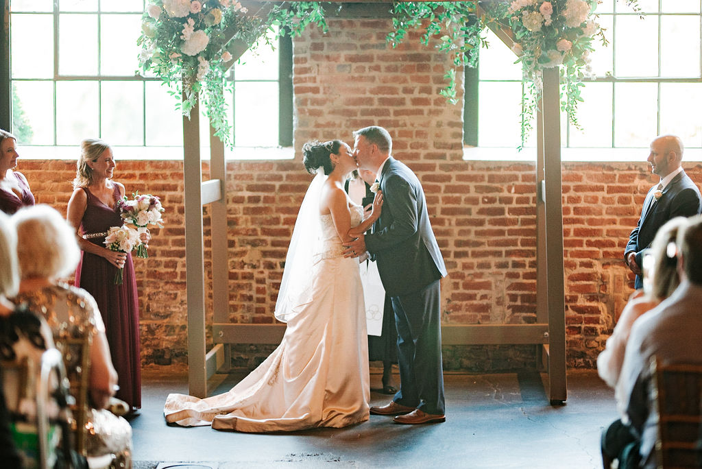 bride and groom kissing at the alter at Inn at the Old Silk Mill