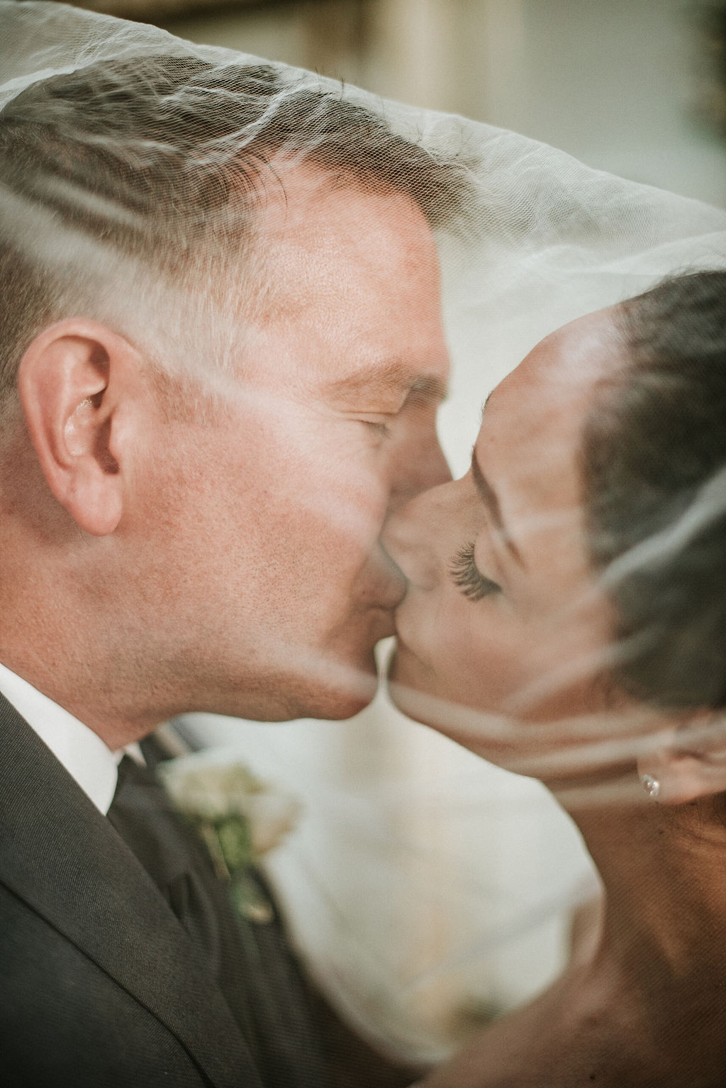bride and groom kissing under veil at Inn at the Old Silk Mill