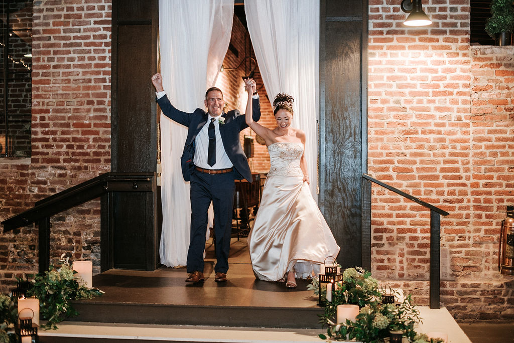 bride and groom holding hands as the enter reception at Inn at the Old Silk Mill