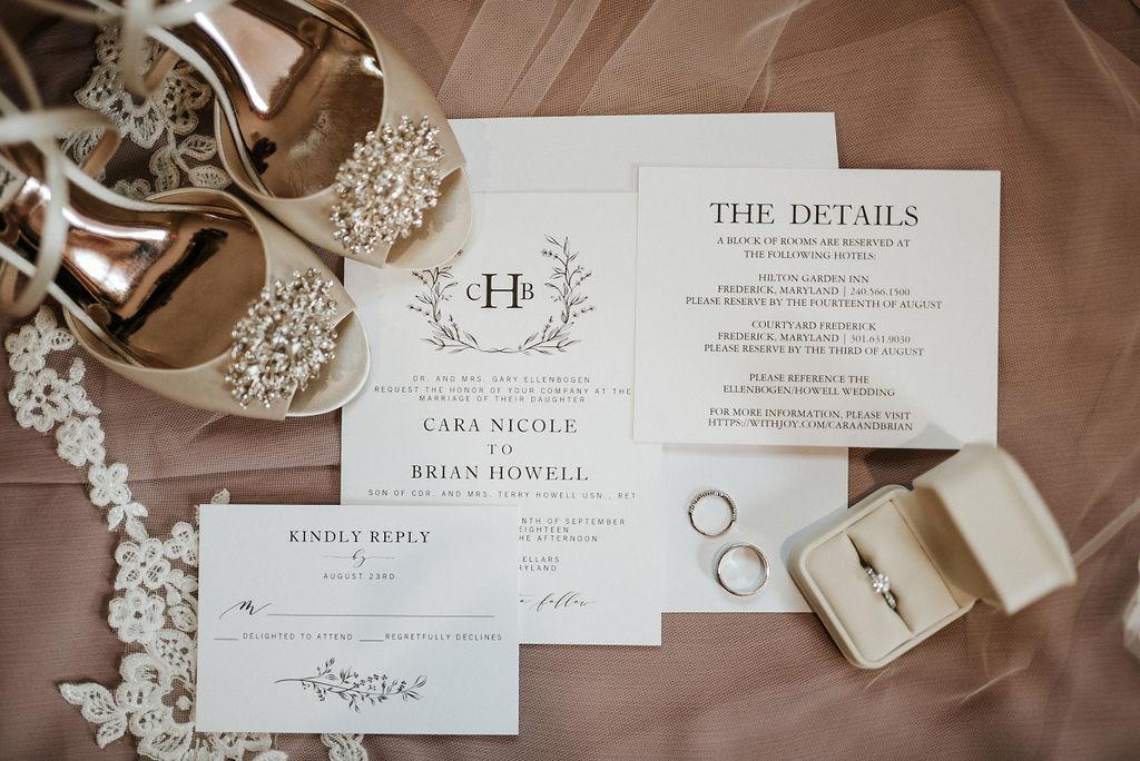 detail shot of shoes and wedding invitations and wedding rings at Linganore Winecellars