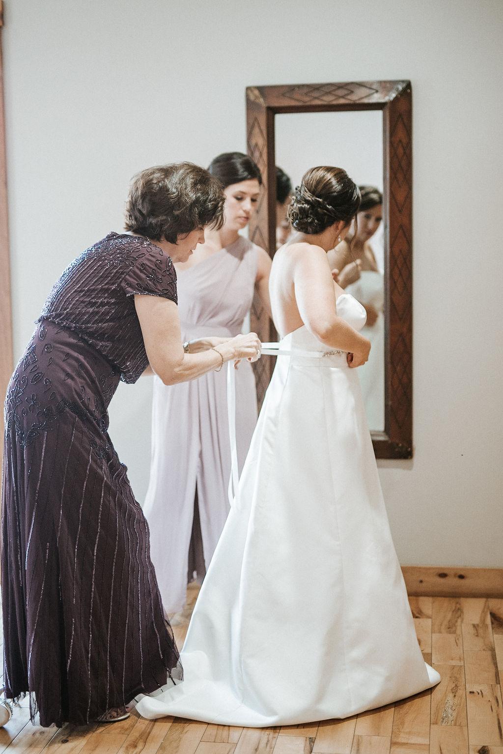 bride getting into wedding dress at Linganore Winecellars
