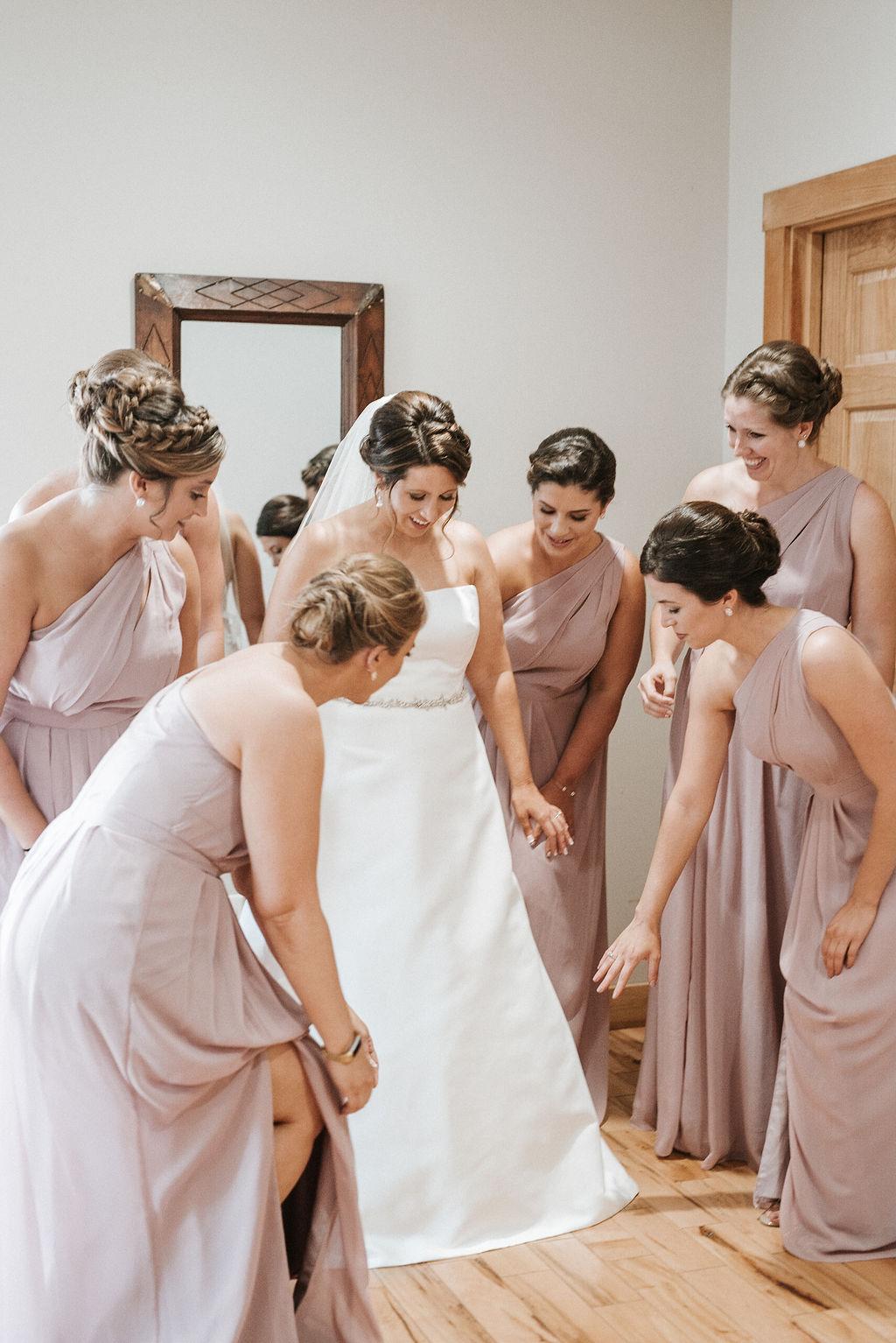 bridesmaids helping bride get ready at at Linganore Winecellars