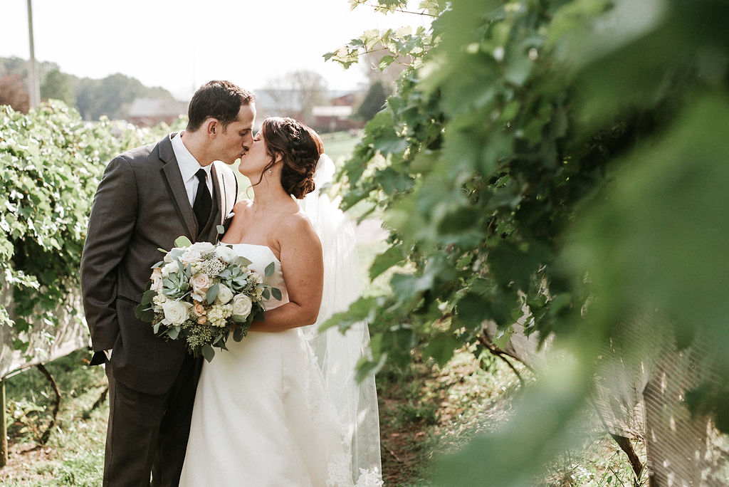 bride and groom kissing by vines at Linganore Winecellars