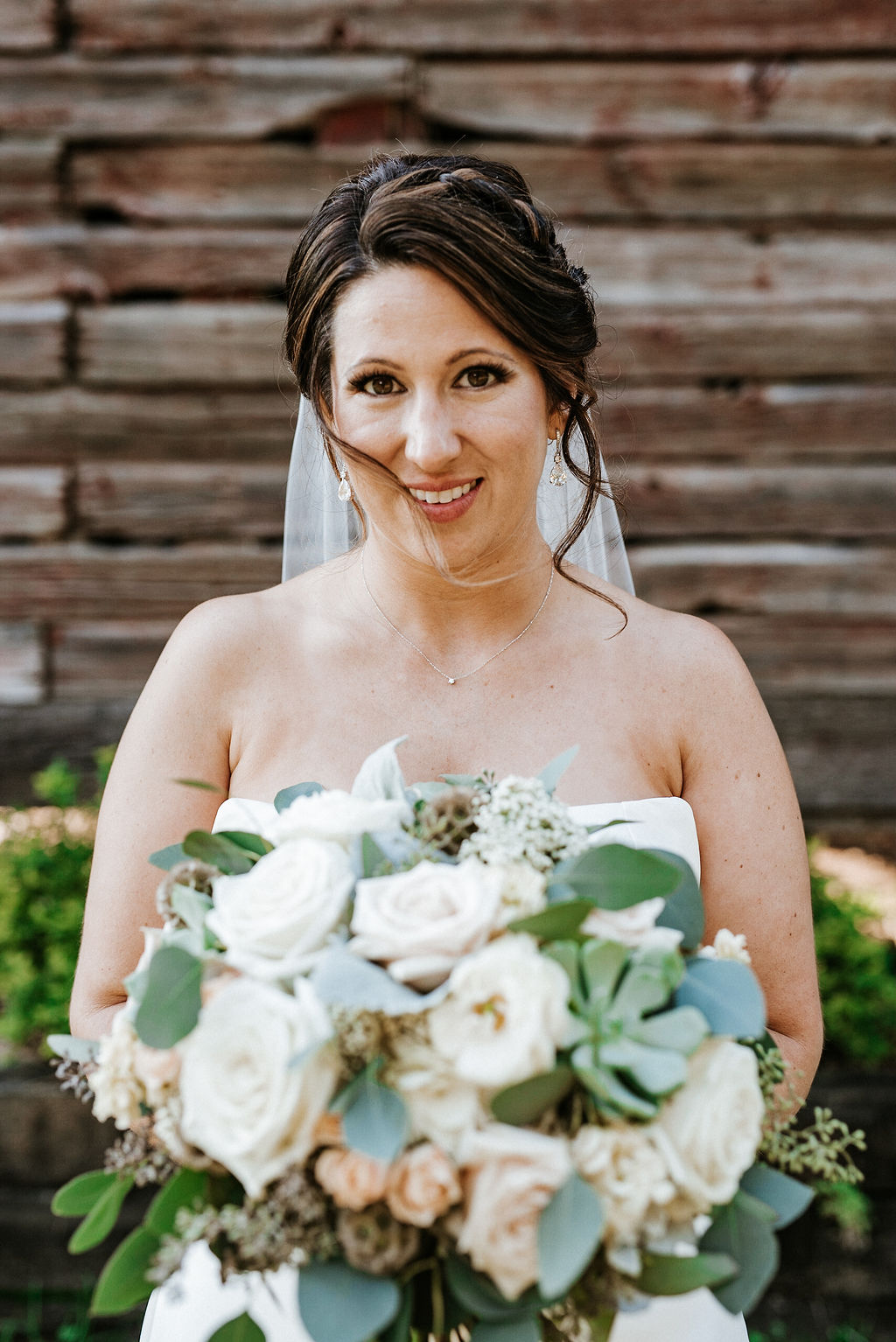bride smiling in front of barn at Linganore Winecellars