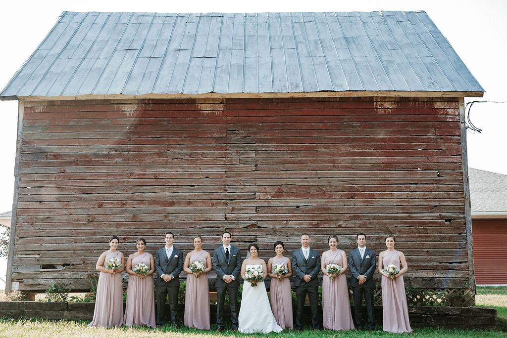 wedding party posing and smiling at Linganore Winecellars