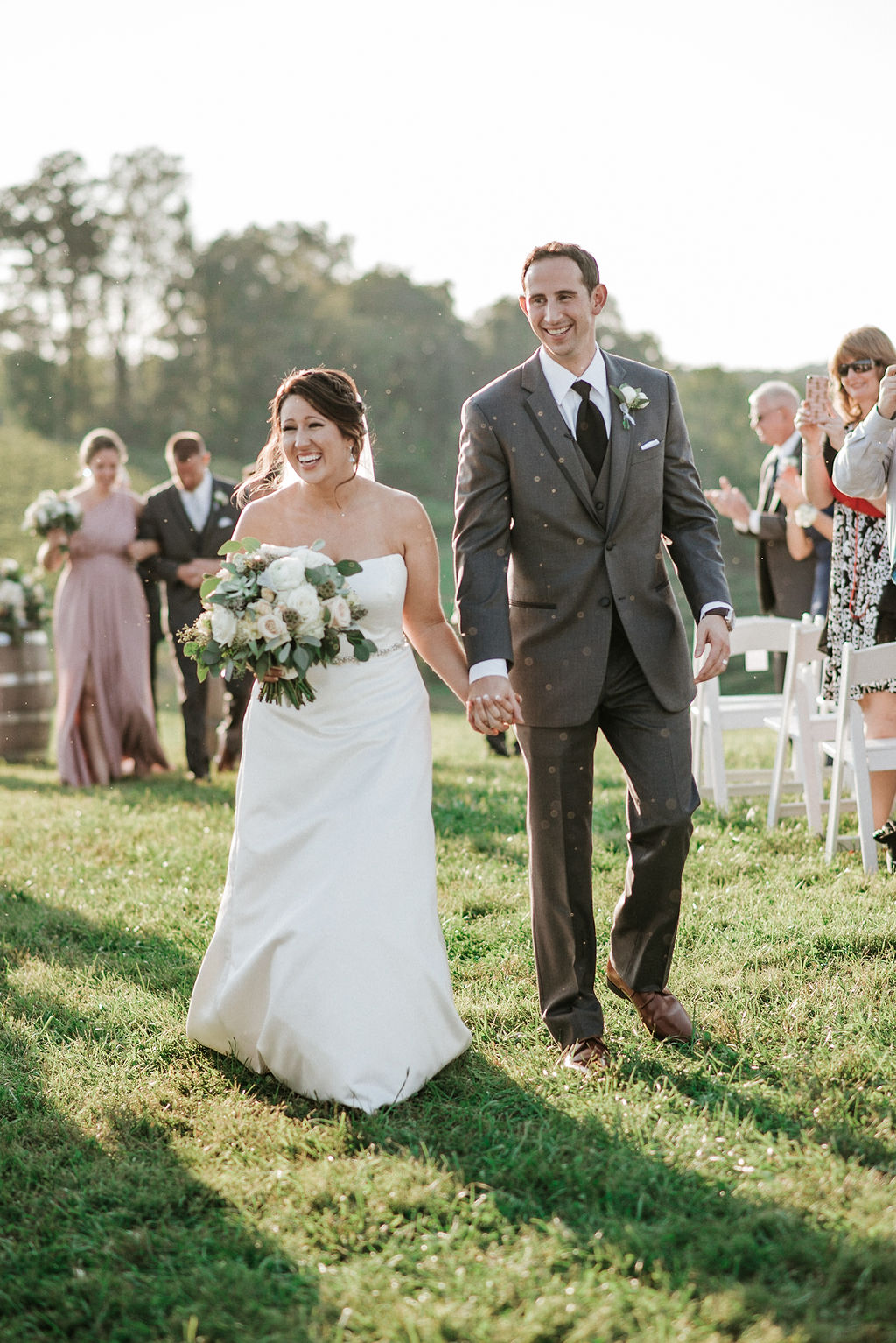 bride and groom smiling as they walk down the aisle at Linganore Winecellars