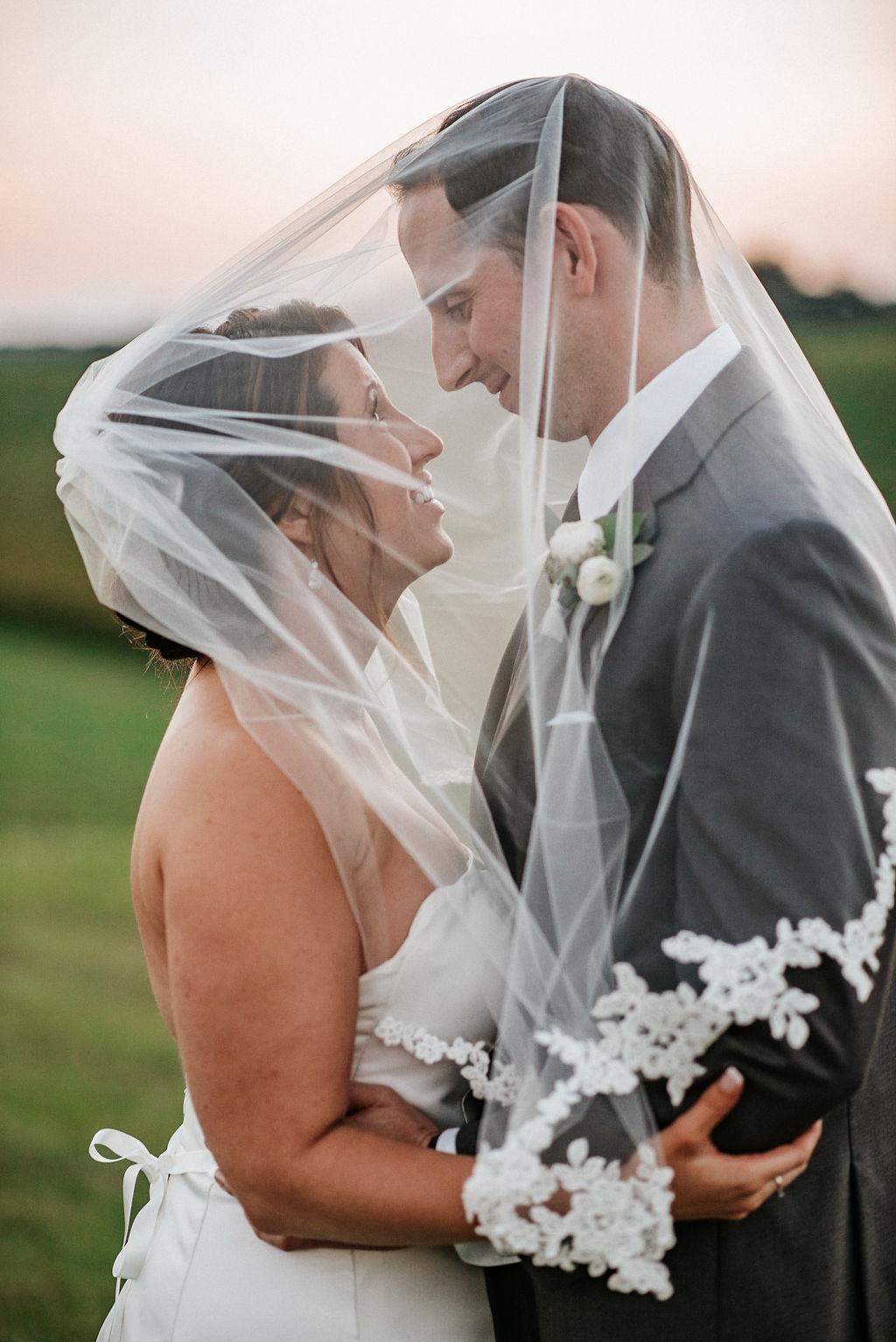 bride and groom smiling under bride's veil at Linganore Winecellars