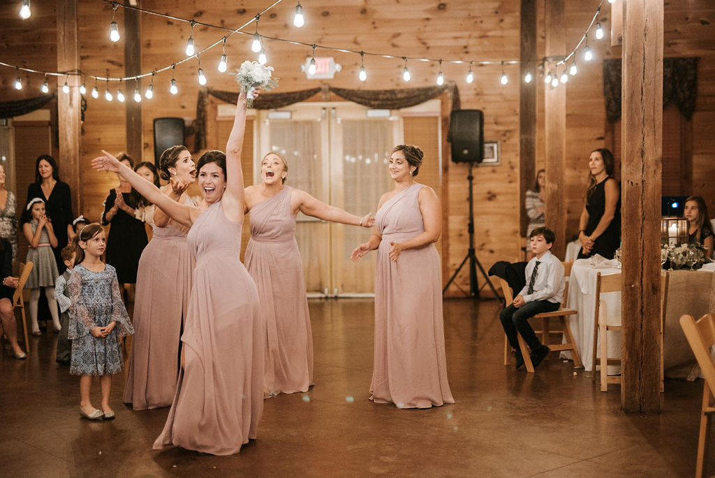 bridesmaids catch the bouquet at Linganore Winecellars