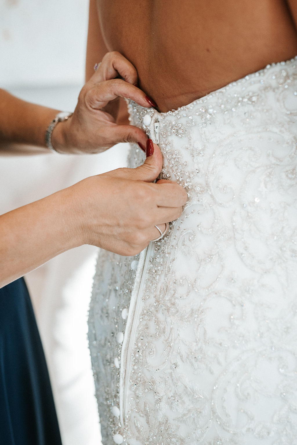 Mother of the Bride zipping up wedding dress at Blue Valley Vineyard