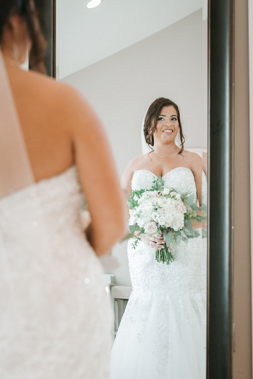 Bride looking at herself in the mirror at Blue Valley Vineyard