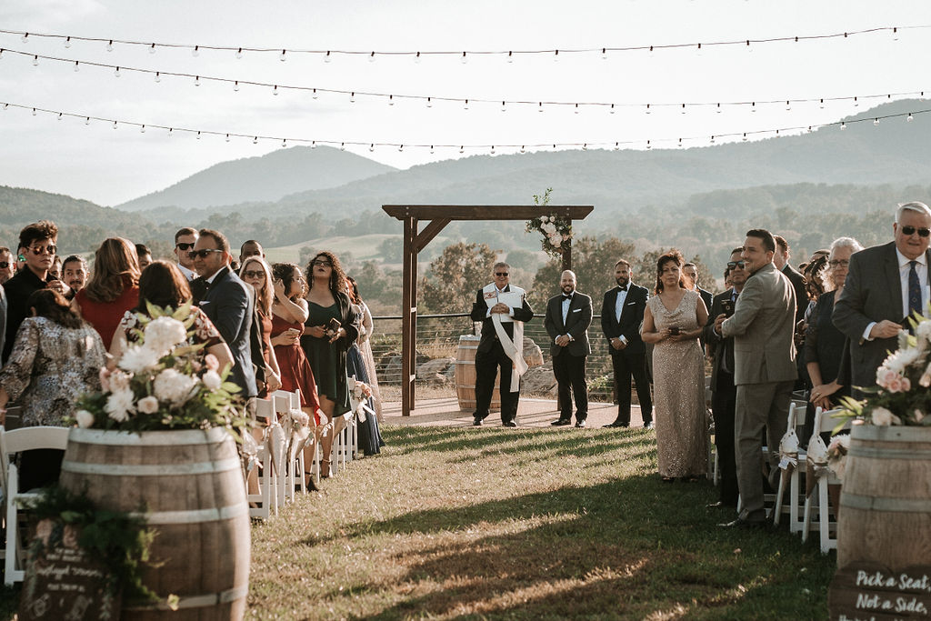 Guests standing up to see the bride at Blue Valley Vineyard