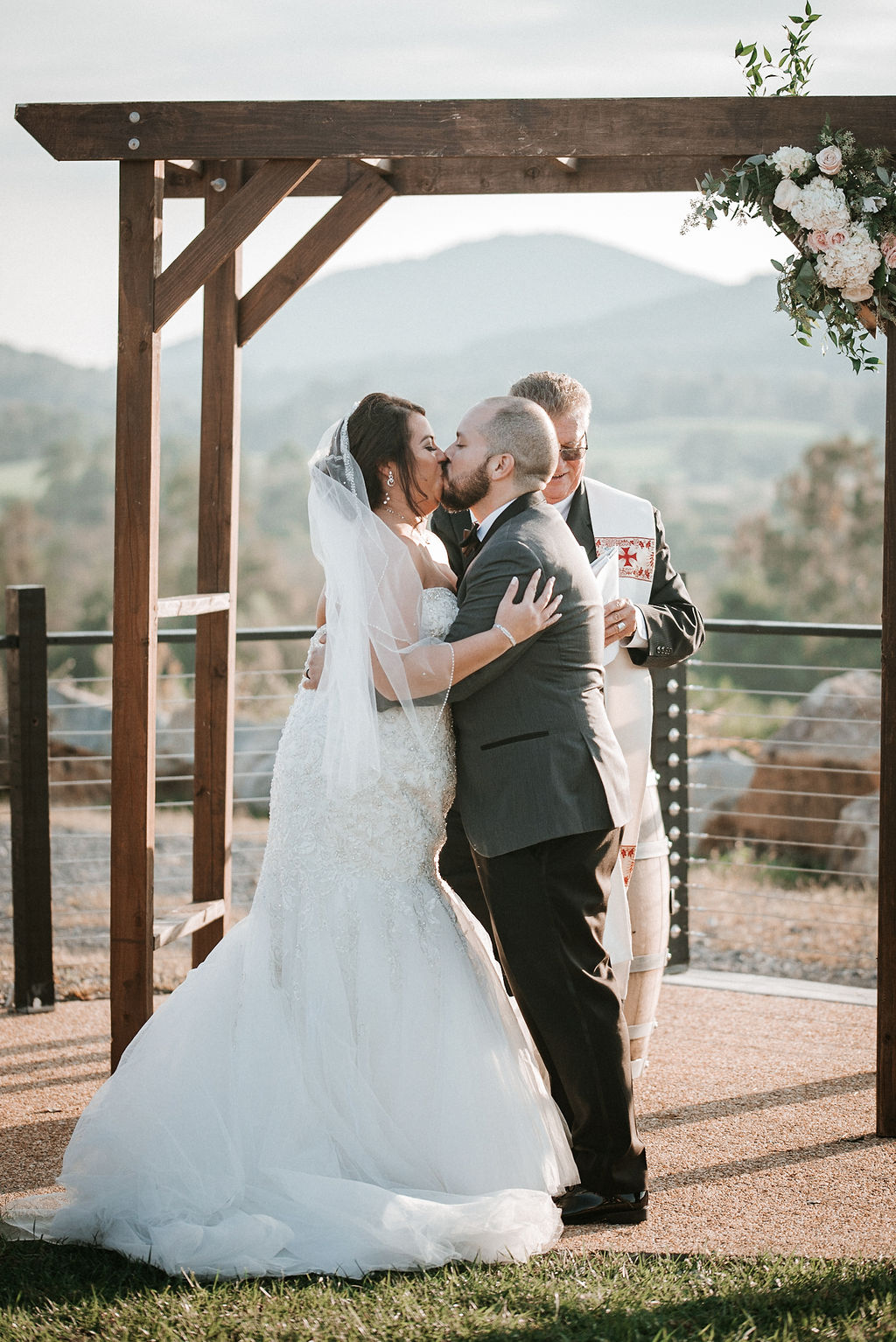 bride and groom kissing at the alter at Blue Valley Vineyard