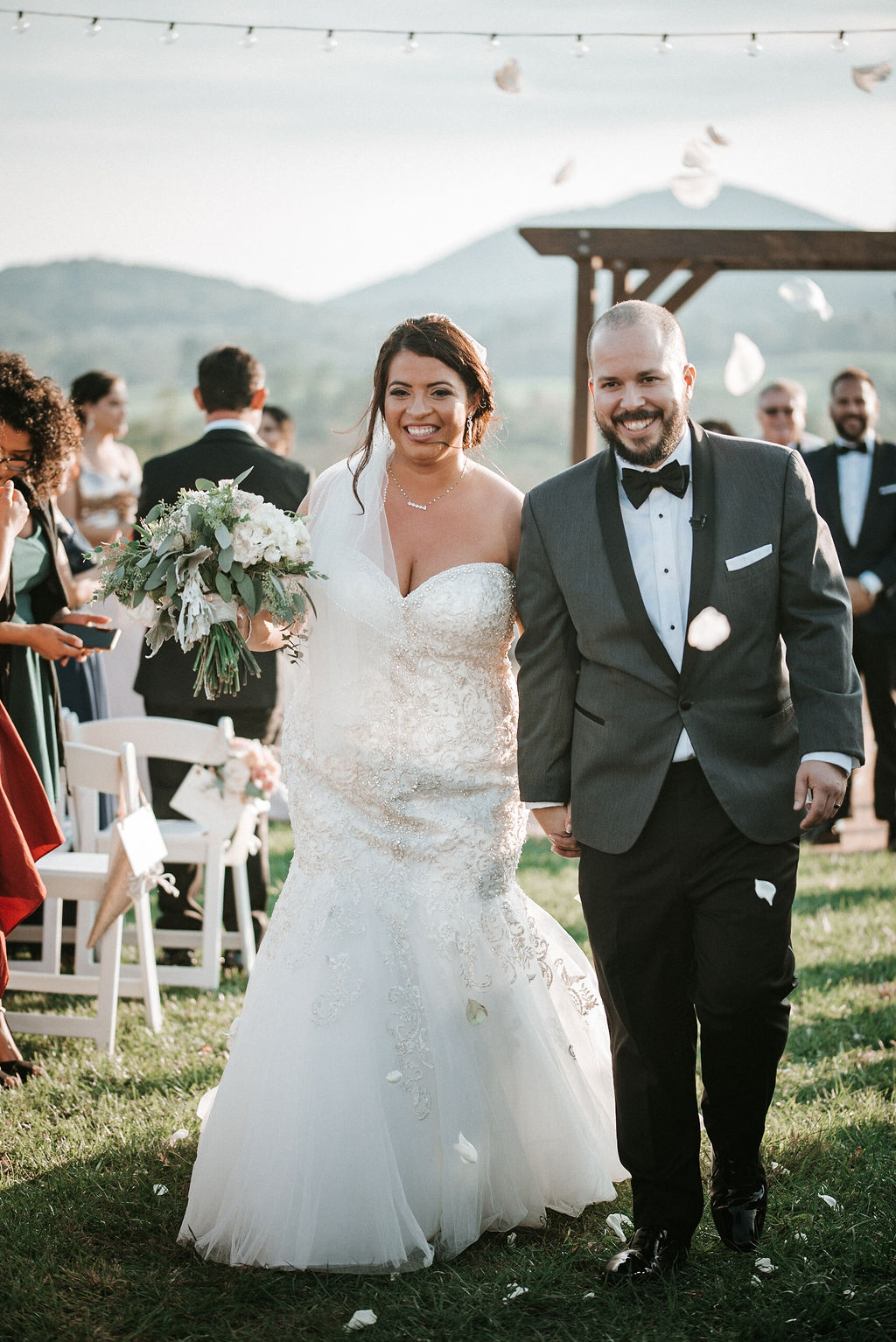Bride and Groom smiling as they walk up the aisle at Blue Valley Vineyard