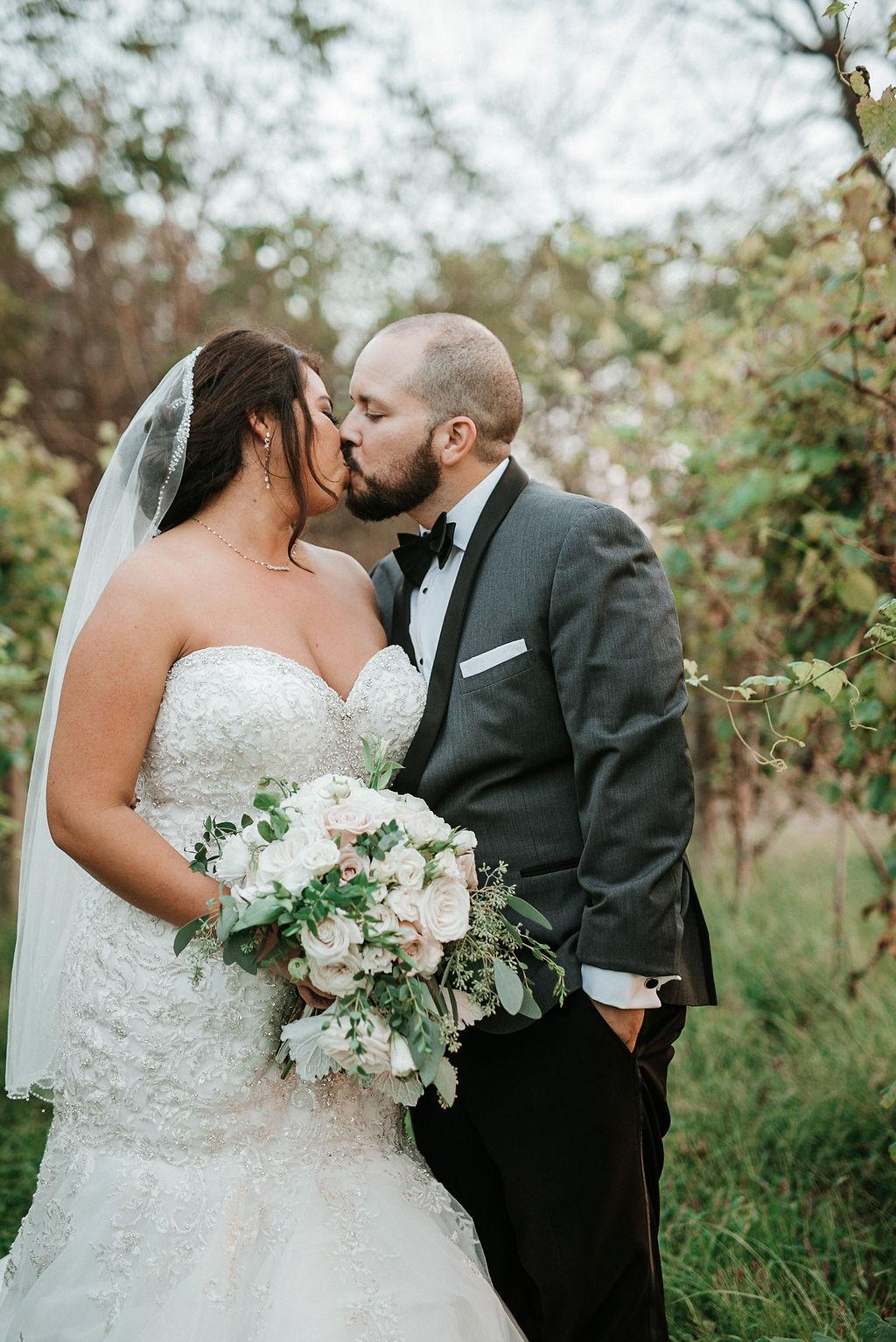 Bride and Groom Kissing in the Vineyards at Blue Valley Vineyard