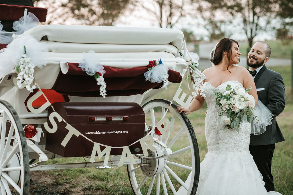 Bride and Groom Smiling next to a carriage at Blue Valley Vineyard