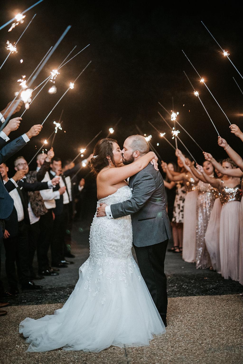 bride and groom kissing under sparklers at Blue Valley Vineyard